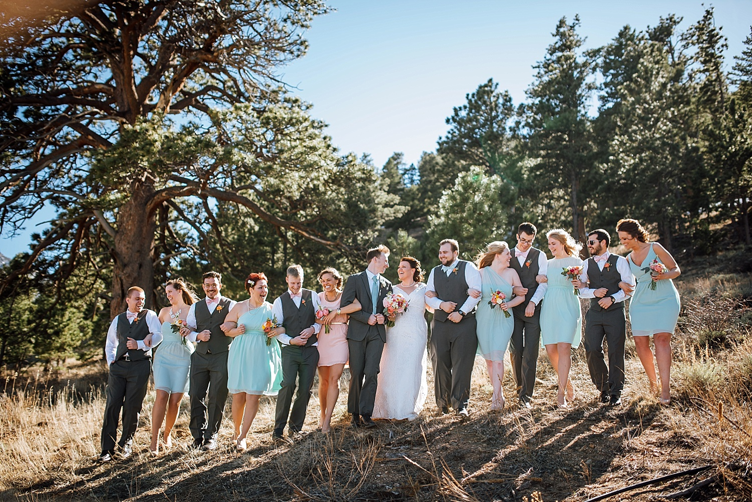 The blush and tiffany blue color scheme is perfect for a large wedding party and mountain wedding! Mary's Lake Lodge up in Estes Park is such a beautiful wedding venue! Photo by Maddie Mae Photography