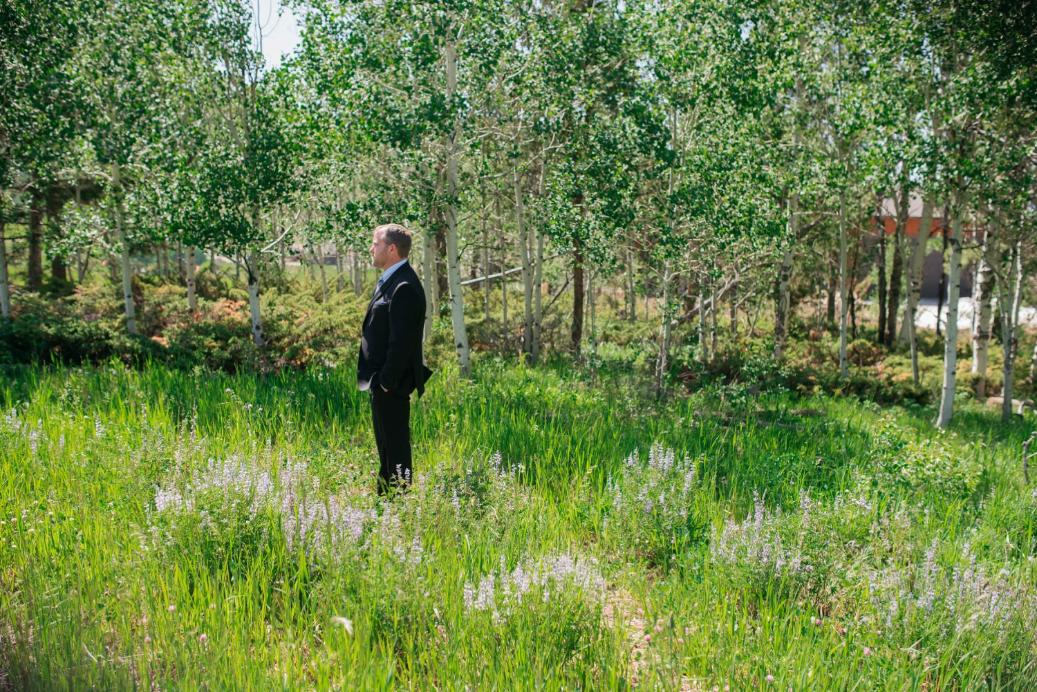 The groom waiting for his bride and their first look in the middle of a mountain meadow! How romantic! Photo by Maddie Mae Photography