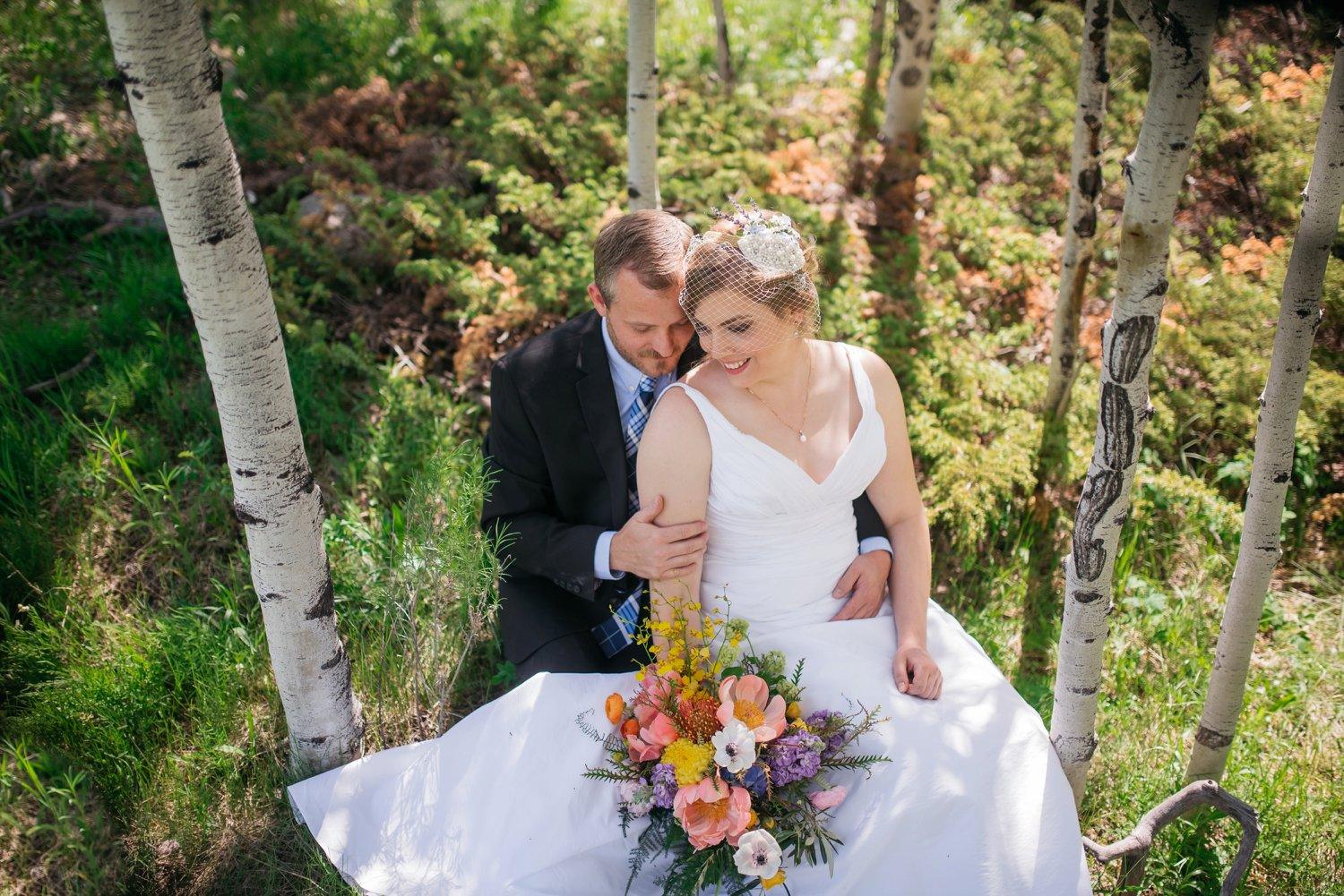 So cute! The bride and groom sitting down among the aspen trees in a mountain meadow! I really want a Colorado mountain wedding! Photo by Maddie Mae Photography