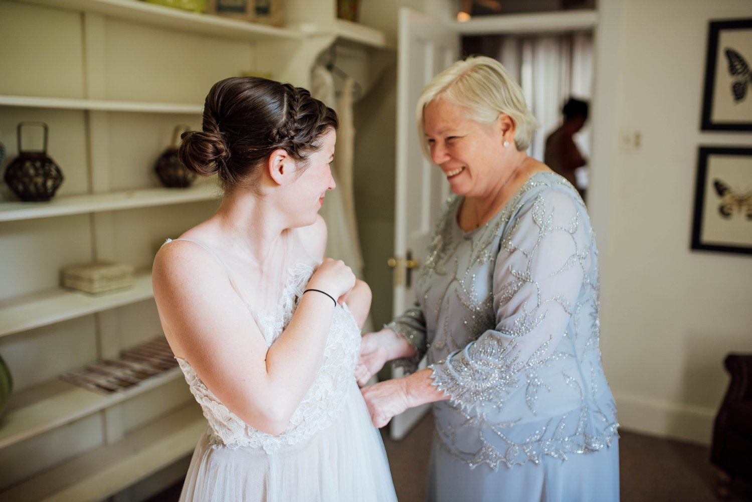 Such a sweet moment of a bride and her mom getting ready for the big day!Photo by Maddie Mae Photography