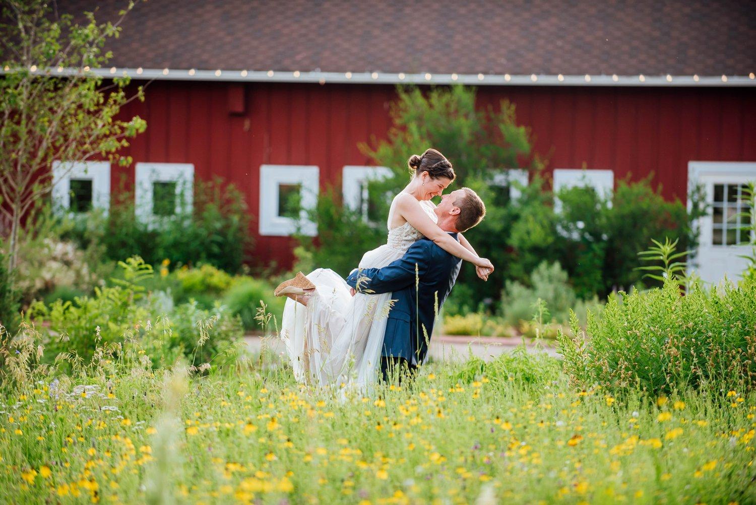 I love the idea of the groom holding and swinging the bride around in front of the bright red barn at the Dever Botanic Gardens at ChatfieldPhoto by Maddie Mae Photography
