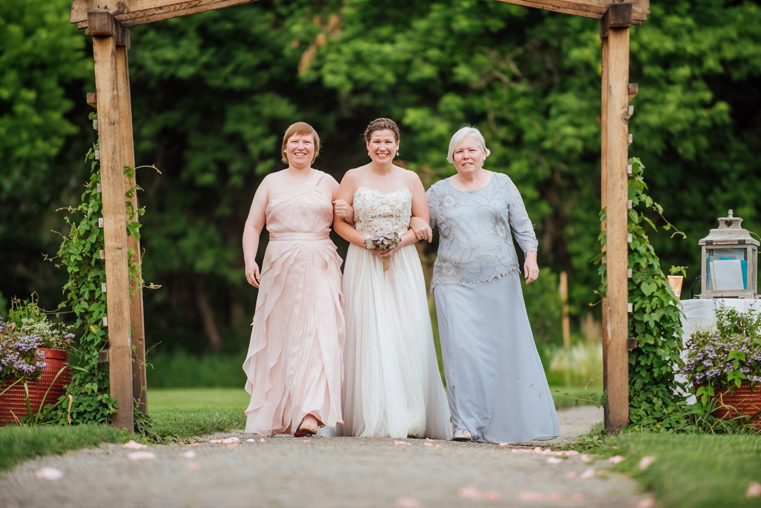 I love nontraditional weddings where the bride is being walked down the aisle by her family.Photo by Maddie Mae Photography