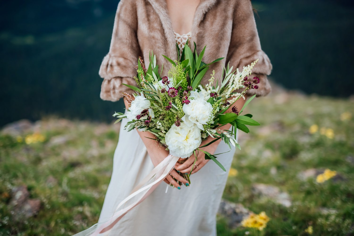 This wildflower bouquet looks so beautiful against her fur coat and the mountain background. Photo by Maddie Mae Photography