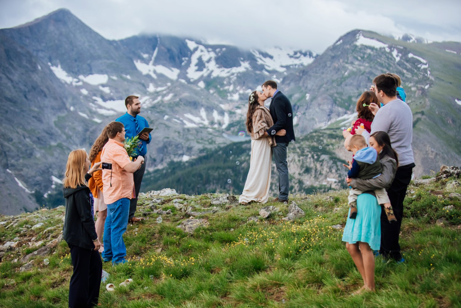 The wedding ceremony of the edge of a cliff is beautiful - I love the snow on the mountains in the background! Photo by Maddie Mae Photography