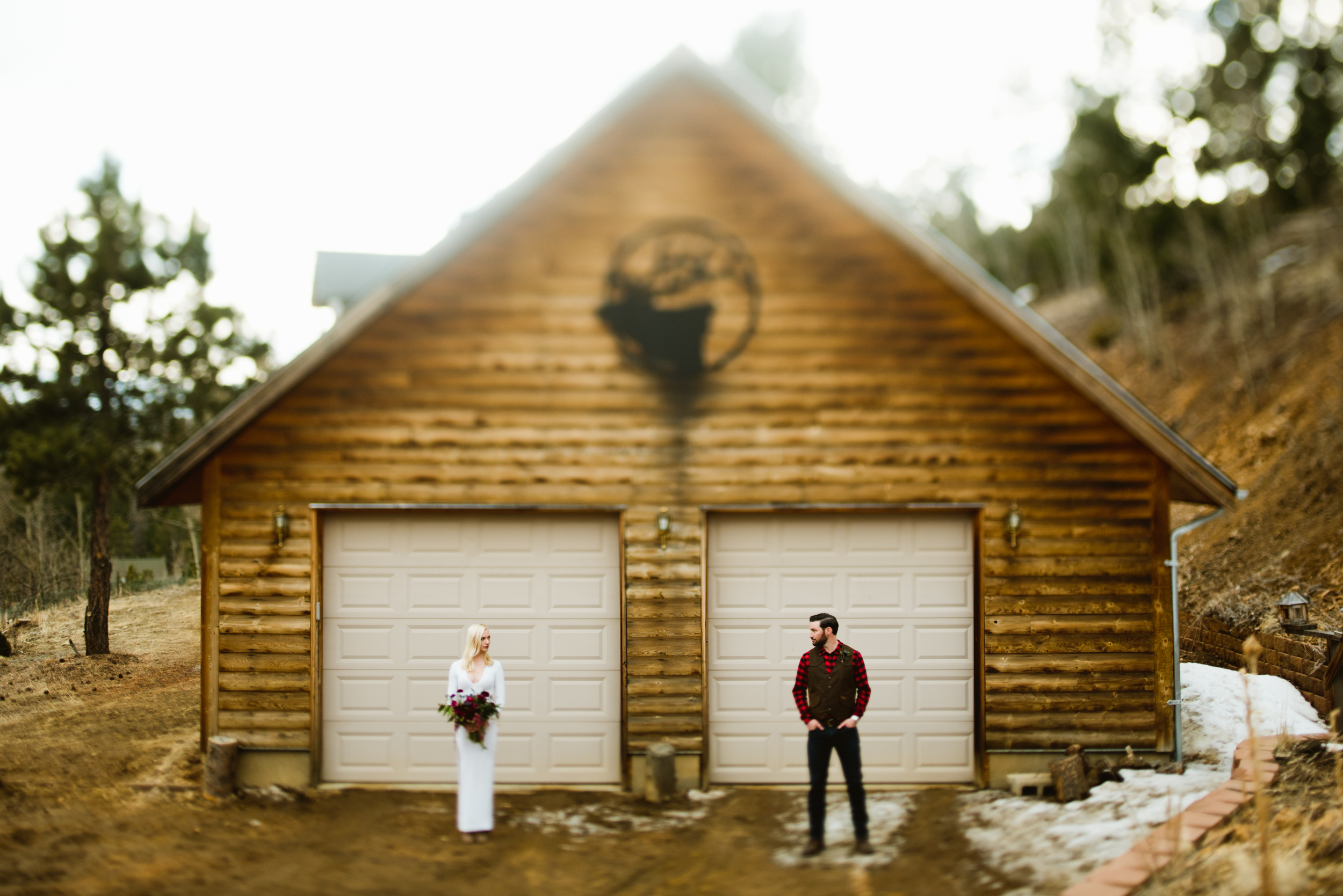 A simple and elegant pose of a bride and groom in front of a rustic cabin for their adventurous mountain elopement in Black Hawk, Colorado. | Photo by adventure elopement photographer, Maddie Mae.