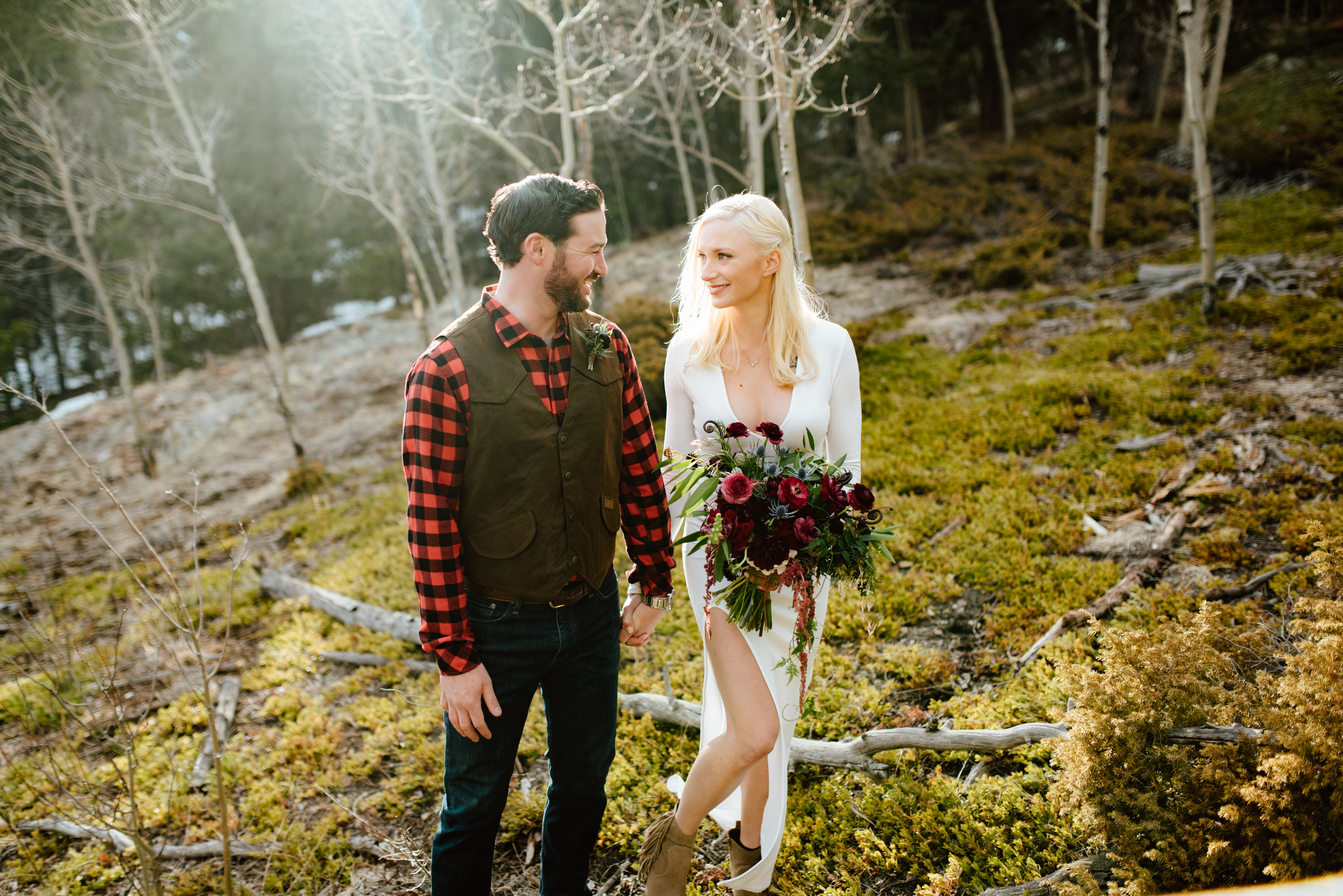 This adventurous couple looks incredible surrounded by the sun kissed aspen trees in a forest near the mountains of Black Hawk, Colorado. What a peaceful elopement! | Photo by adventure elopement photographer, Maddie Mae.