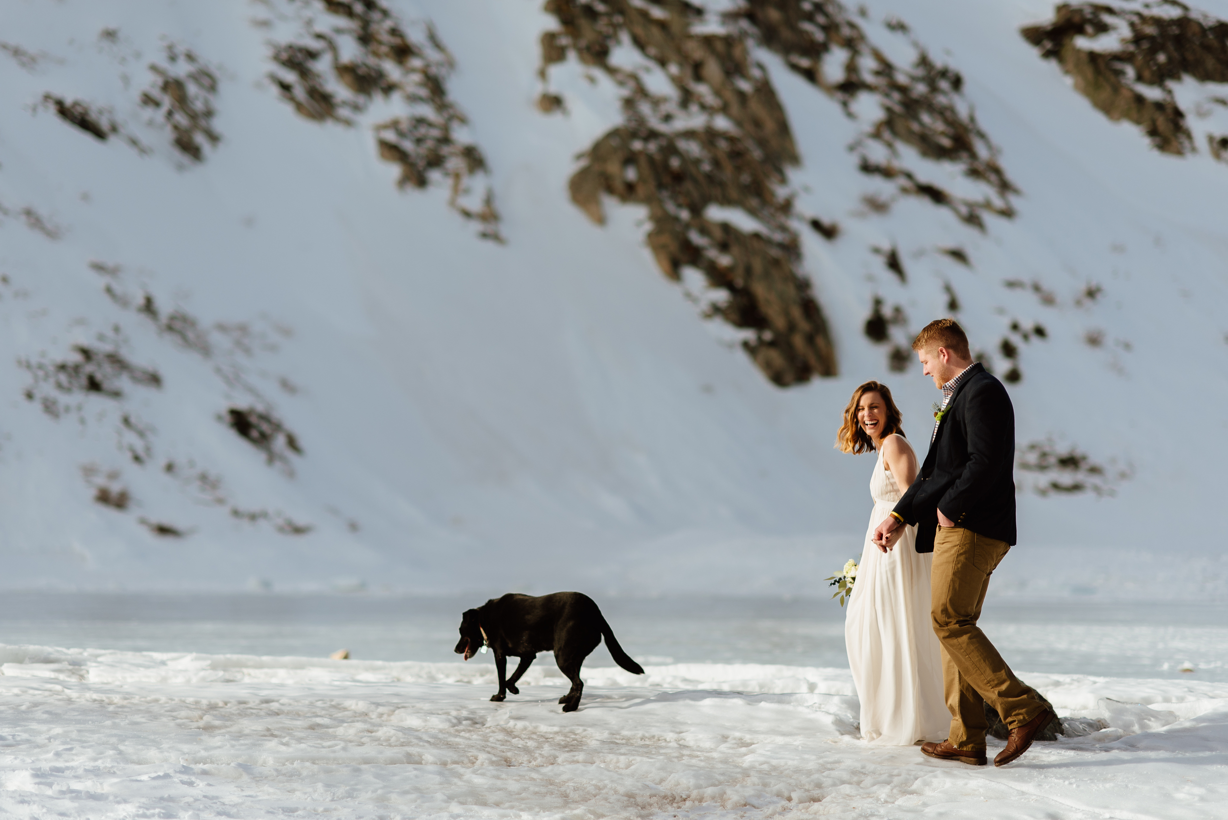 What an adorable wedding photo of the bride and groom frolicking in the snow with their dog! I love the idea of an intimate,winter wedding in the Rocky Mountains!| Mountain wedding photos by intimate, elopement photographer, Maddie Mae.