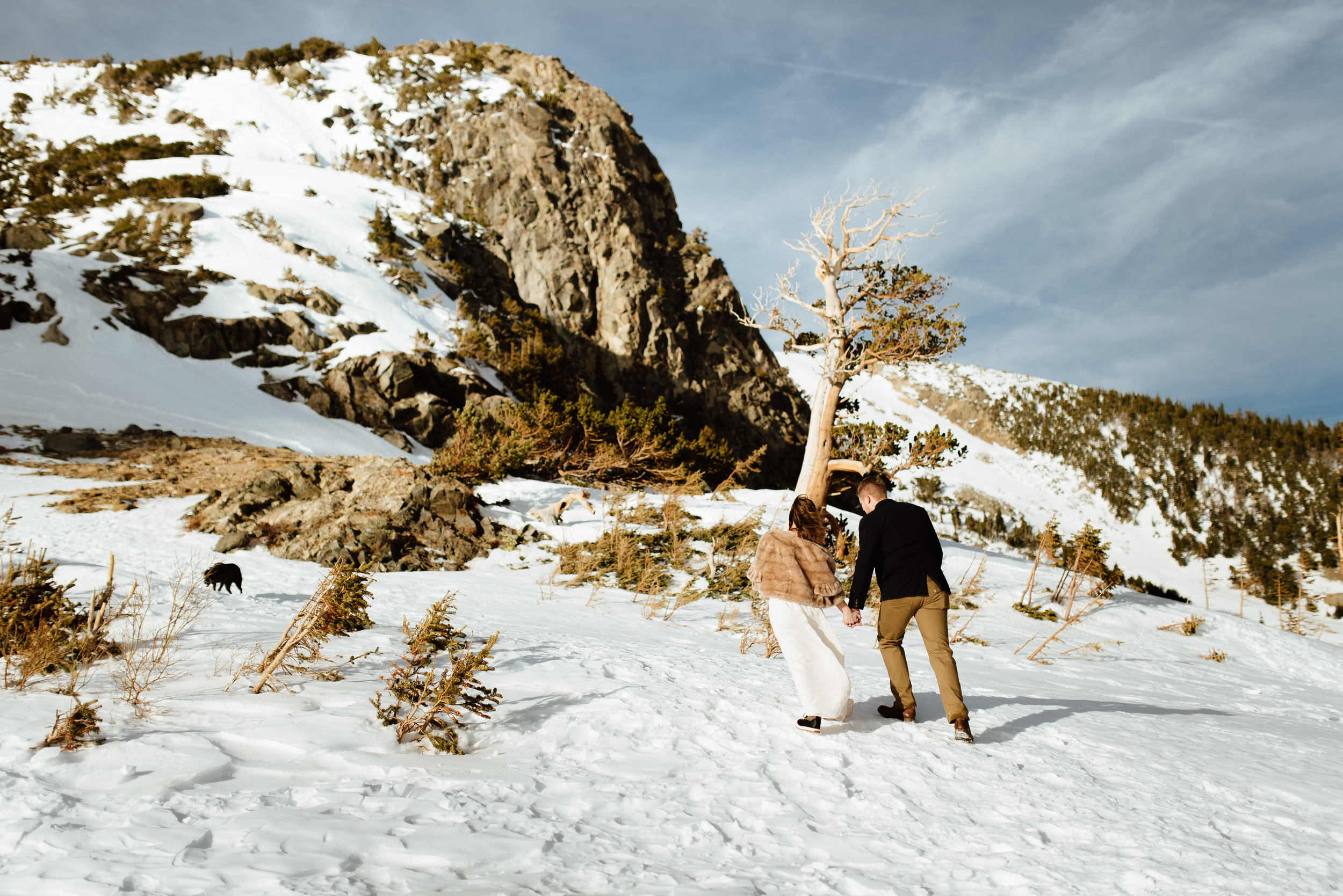 Kelsie and Tyler are on their way up to the romantic and intimate ceremony spot. I love the wild and whimsical snowy forest in Idaho Springs, Colorado.| Mountain elopement pictures by intimate wedding photographer, Maddie Mae.