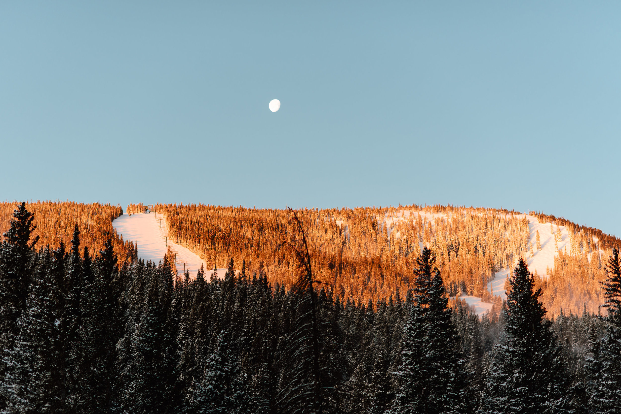 The way the sun it kidding this snowcapped mountain ski area is so breathtaking. I love when the moon is still out in the early morning when you're in nature. What a perfect spot for an engagement photoshoot!| Adventurous engagement photos by Colorado mountain wedding photographer, Maddie Mae.