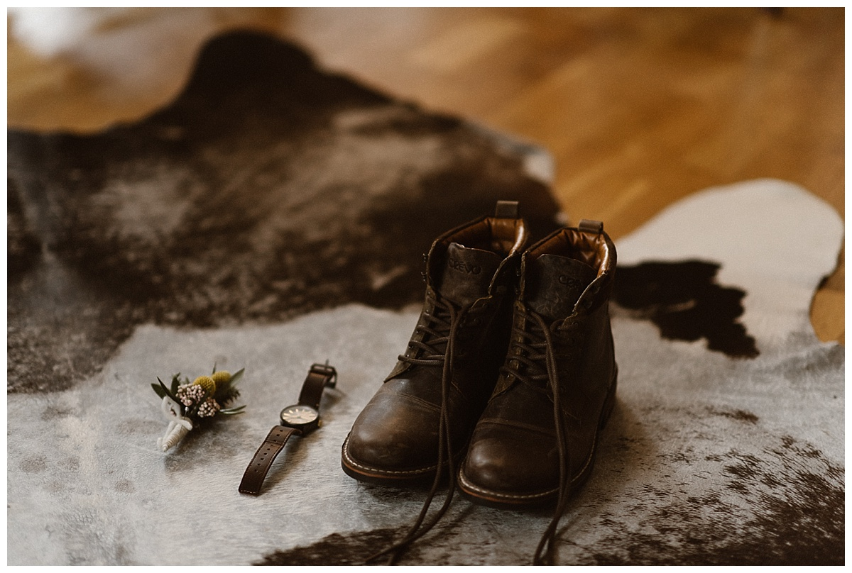 Not knowing what kind of weather they may encounter, Tim opted for a comfortable pair of hiking boots for their intimate Icelandic elopement and donned only simple additional details like a bright yellow boutineer and his classic leather watch. Photo by intimate wedding photographer Maddie Mae.