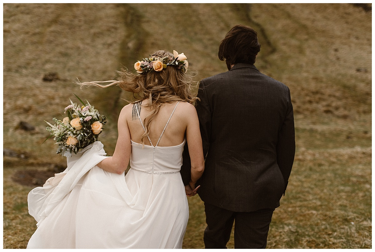 With the wind blowing, they meandered their way up the grassy hillside with Julie's flowers glowing like a halo from her hair. This intimate Seljalandsfoss waterfall elopement photographed by traveling wedding photographer Maddie Mae.