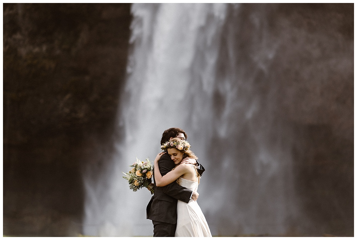 Their love as epic as Seljalandsfoss waterfall behind them, they paused as though no one was looking to share an intimate embrace, the kind where their love could be felt for miles away. This epic Icelandic elopement photographed by Maddie Mae Photography.