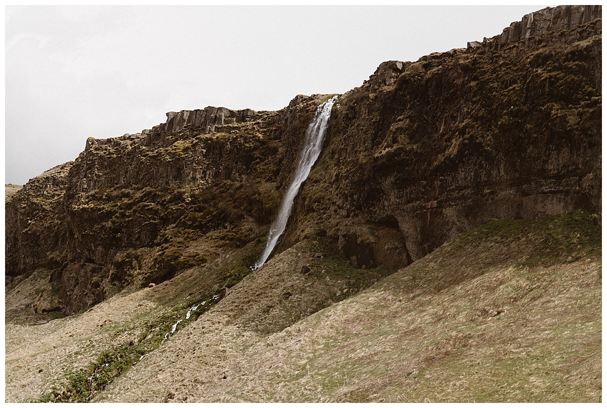Seljalandsfoss waterfall cuts deep through the jagged Icelandic hillsides giving way to lush green grass below, a stunning location for an intimate elopement or wedding ceremony. Photo by traveling photographer Maddie Mae.