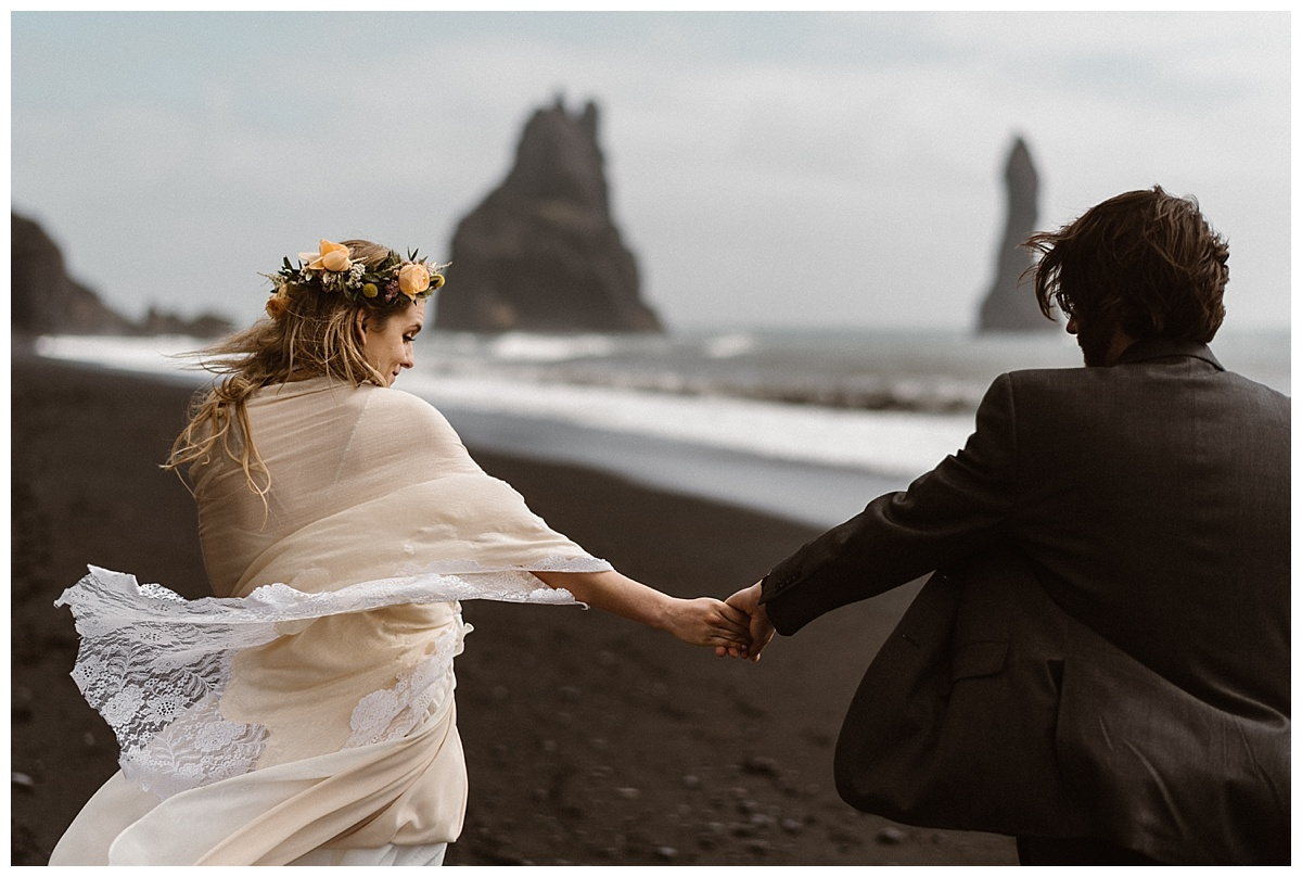 Wind blown and so in love, Julie and Tim's love radiated far beyond Reynisdrangar beach. Her lacy vintage shawl looking like she was going to blow away. This stunning Iceland elopement photographed by intimate wedding photographer Maddie Mae.