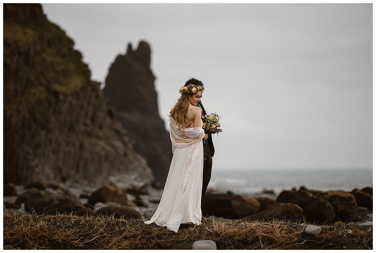 Taking in the epic views of Reynisdrangar's rocky beach Julie and Tim got ready to hit their next location on their whirlwind tour of Iceland for their intimate elopement. Photos by traveling wedding photographer Maddie Mae.