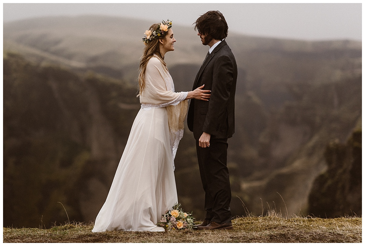 Just moments before saying their intimate wedding vows up above Fjadrargljufur Canyon, Julie and Tim spent their last moments as unwed giggling. Photos captured by wedding photographer Maddie Mae.