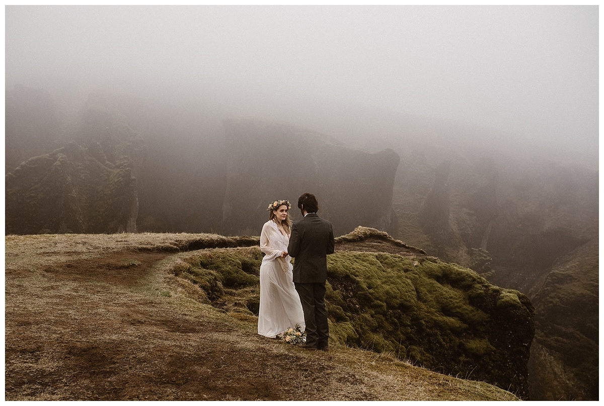 As the fog rolled in on Fjadrargljufur Canyon, it was Tim's turn to say his personalized wedding vows to Julie. The only witness to their intimate Iceland elopement was their photographer, Maddie Mae.