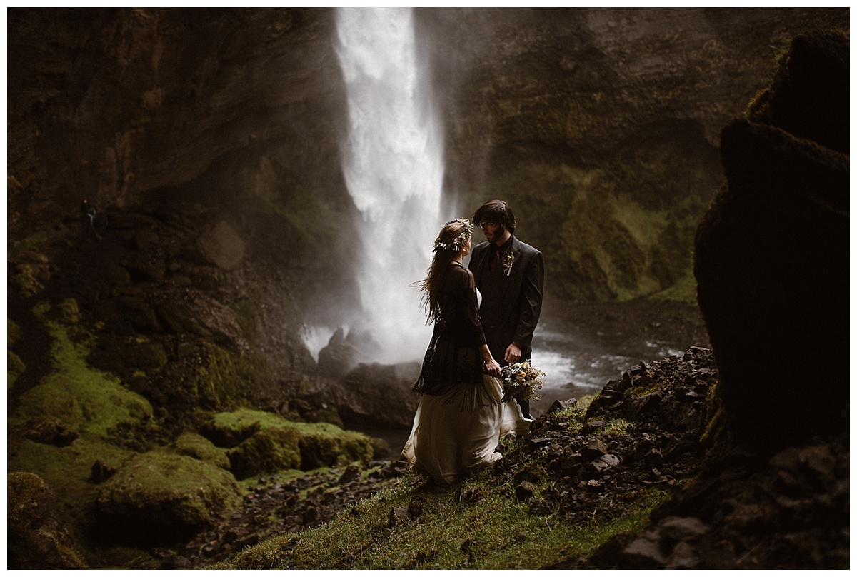 Trekking down lower into the mossy rocks closer to Kvernufoss waterfall, hardly anything could be heard but the rushing water behind them, the sun just peeking through the crevices. Photos of this adventurous Iceland elopement captured by Maddie Mae Photography.
