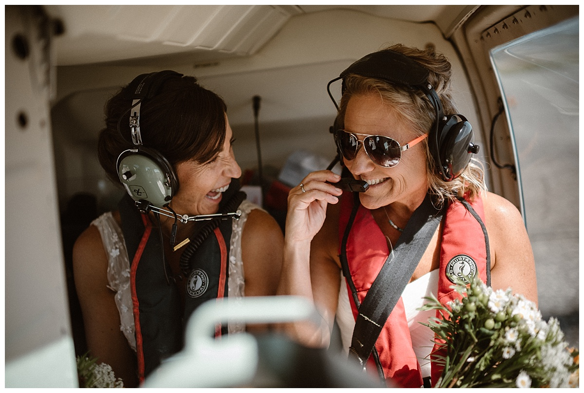 These brides were all smiles while flying high above Tofino BC on their adventurous helicopter elopement. Photos by traveling wedding photographer Maddie Mae.