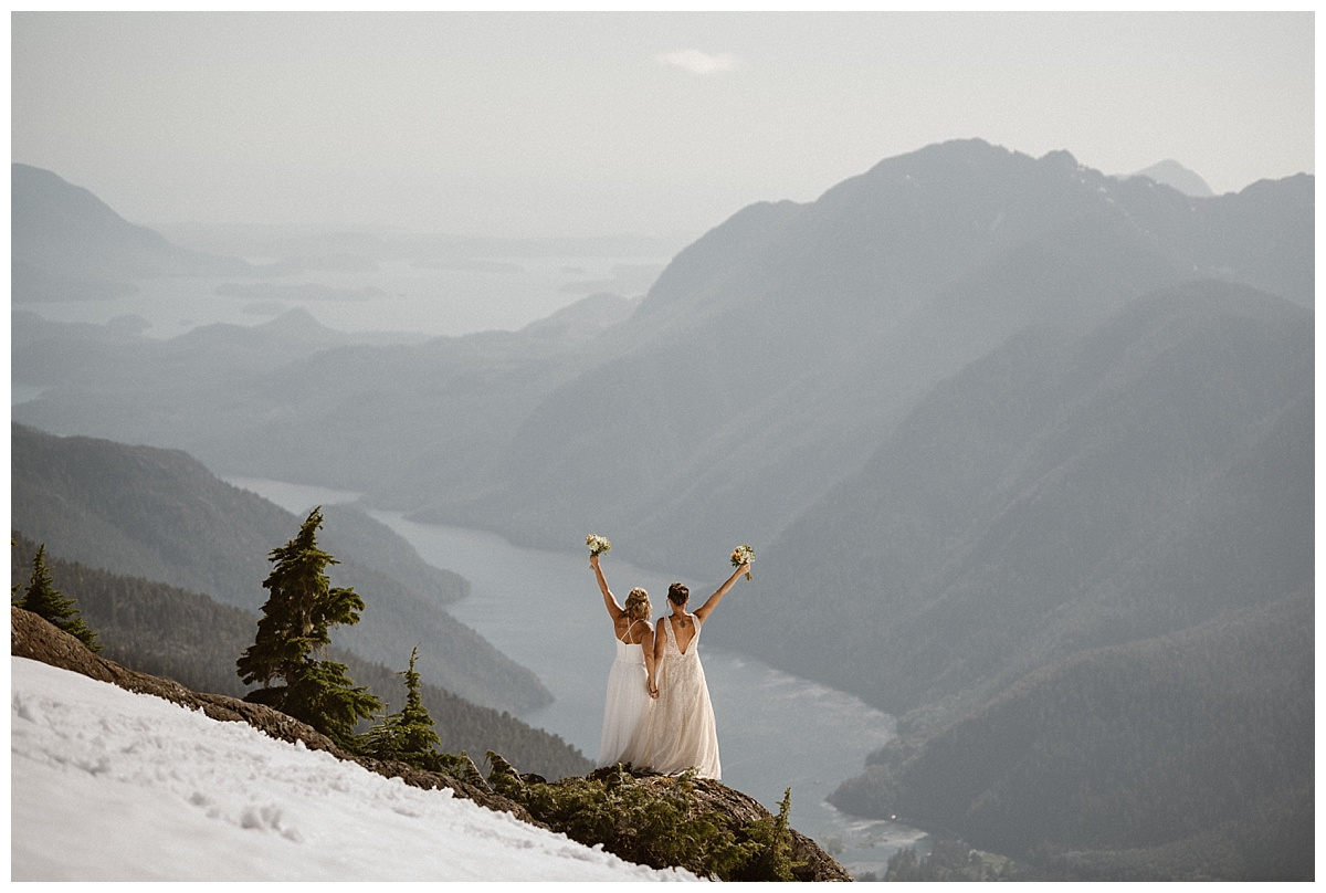 Facing the world and letting out a yelp of delight! Kari and Karin high above Tofino BC were married in an intimate elopement ceremony. They got to their location by helicopter making this easily one of the most adventurous weddings. Photos by Maddie Mae.
