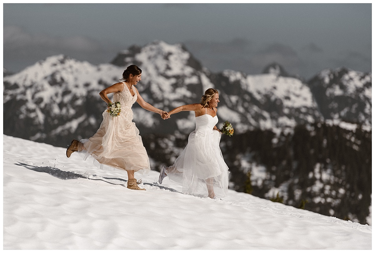 Sinking in the fluffy snow, Kari and Karin ran downhill to the helicopter that was to take them to shell island on their adventurous elopement through Tofino BC. Photos by intimate wedding photographer Maddie Mae.