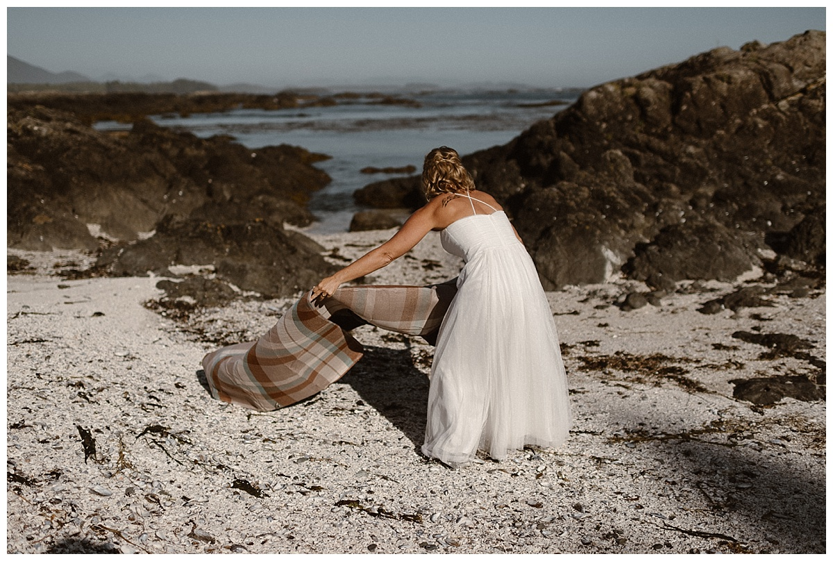 Kari spread a blanket out on the beaches of a deserted island they found in Cox Bay in Tofino BC so she and Karin could enjoy a private picnic amid their adventurous helicopter elopement. Photos of this intimate summer wedding by traveling photographer Maddie Mae.