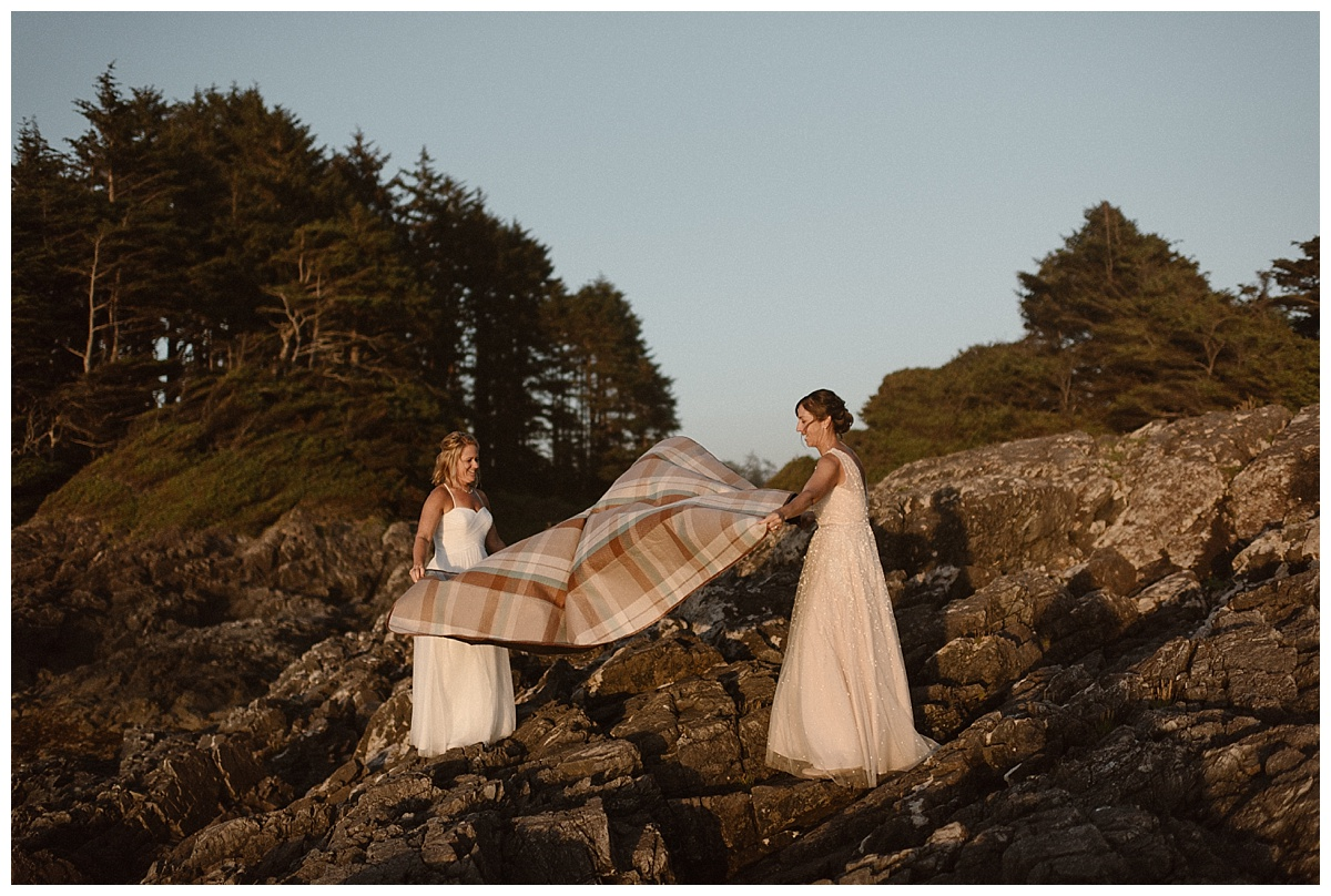 The ladies unfolded a blanket on the rocks above the beach as the sun started to set over Tofino BC. Thinking they were just going to watch the sunset their intimate wedding photographer Maddie Mae had a surprise from back home for the brides.