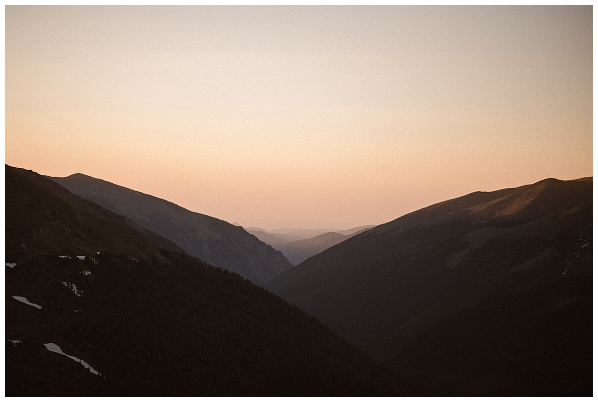 Early mornings in the high alpine terrain just as the sun begins to peek over the mountains the sky lights up a bright peachy pink. The most stunning background for an intimate elopement in the Colorado San Juan Mountains. Photos by traveling wedding photographer Maddie Mae.