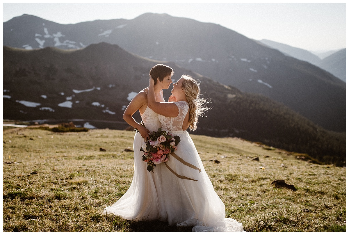 With the sun above them Dona and Malisa glowed like angels in their white tulle dresses up Berthoud Pass in the Colorado mountains. The only witness to their intimate sunrise elopement was their traveling wedding photographer Maddie Mae.