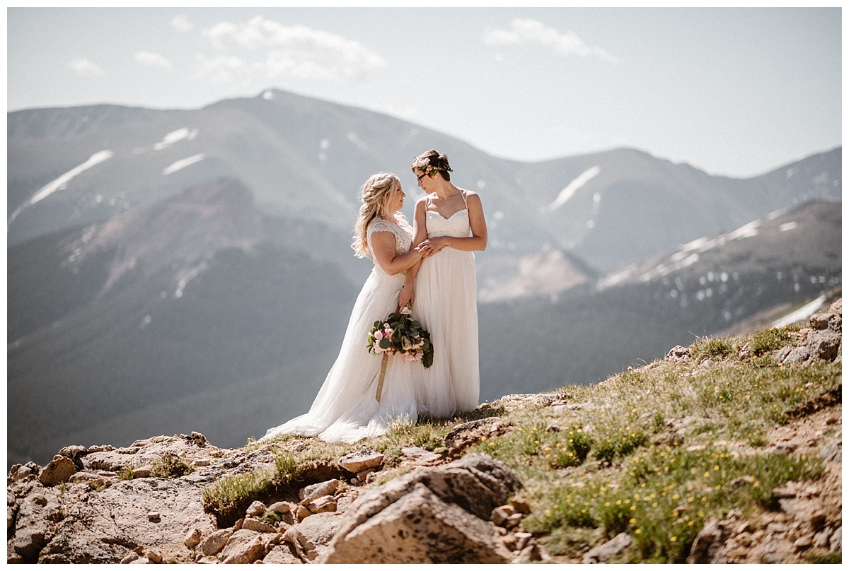 They stopped short of a piles of rocks overlooking the valley below Jonas Pass. These stunning brides hiked around Berthoud Pass after their private elopement ceremony where they said their vows as the sun rose over the Colorado mountains. Their intimate elopement photographed by Maddie Mae.
