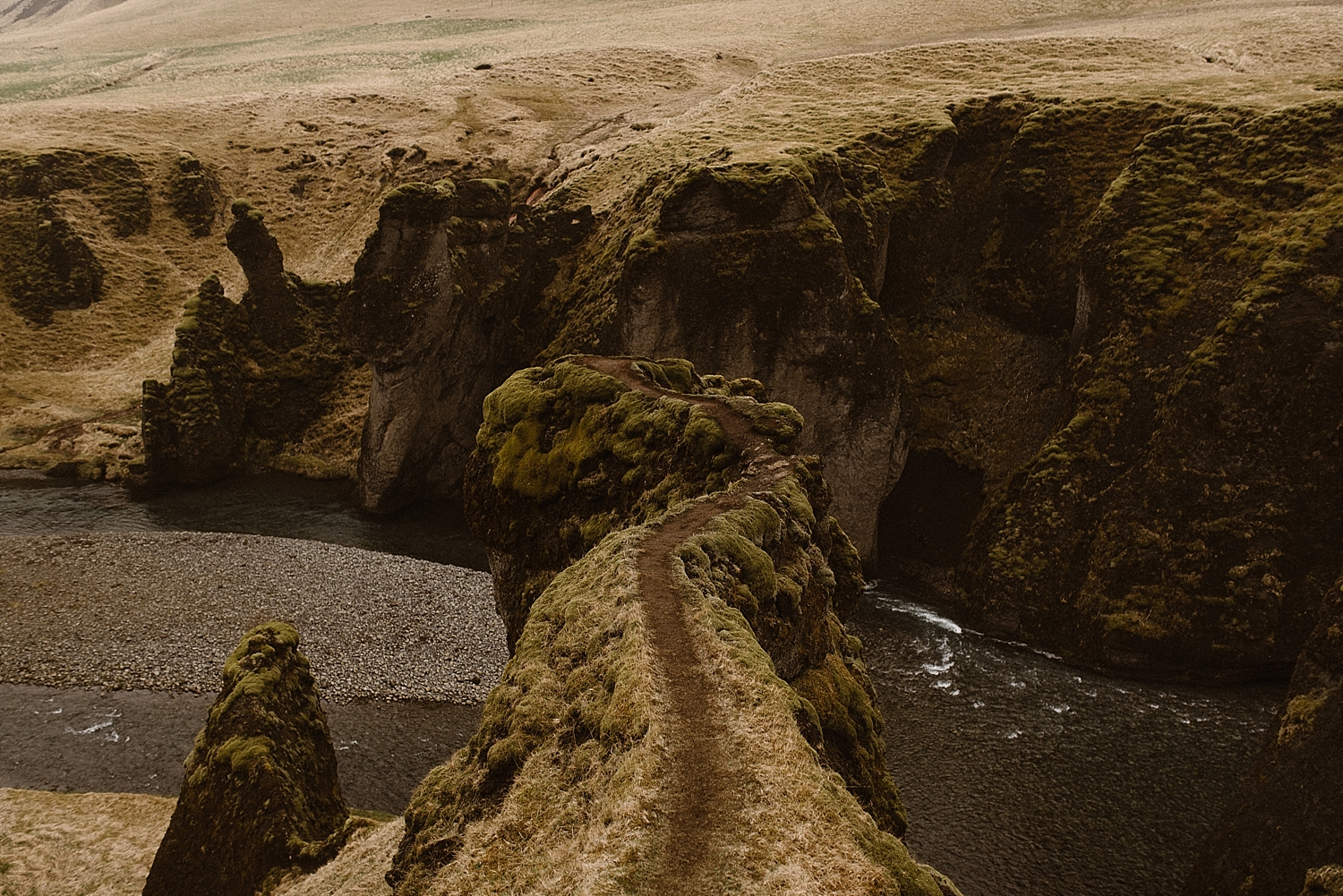 Fjadrargljufur Canyon is riddled with epic trails above the water. Julie and Tim found their adventurous side and began wandering down with the wind at their backs. Photos by intimate wedding photographer Maddie Mae.