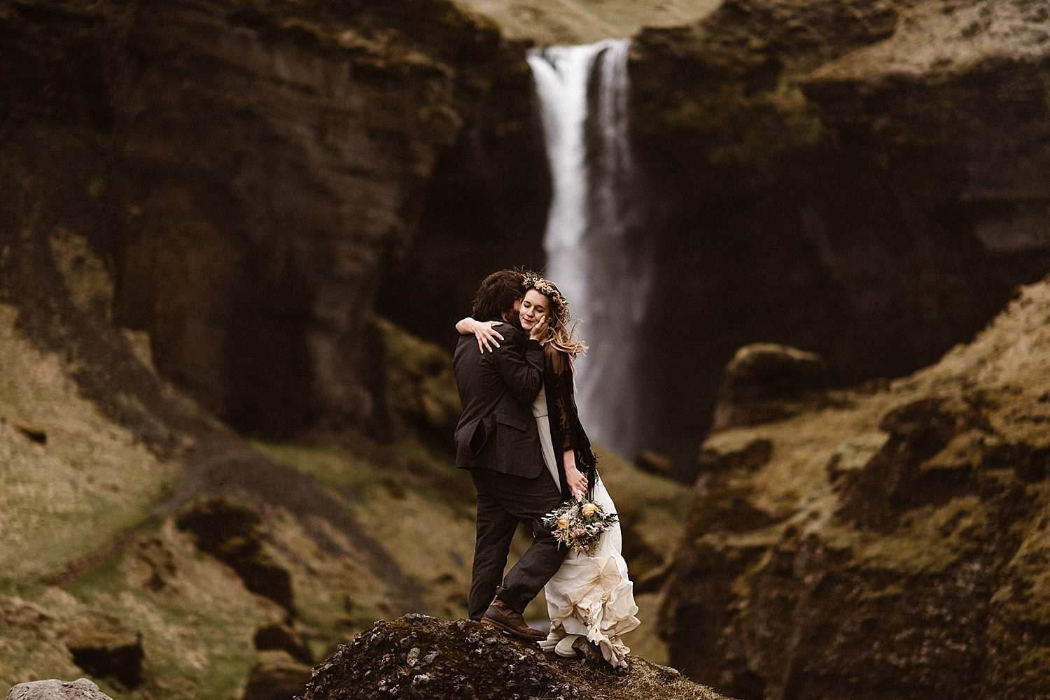 Before wandering closer to Kvernufoss waterfall, Tim and Julie paused in a long embrace, the wind whipping around them. This epic Iceland elopement captured by intimate wedding photographer Maddie Mae.