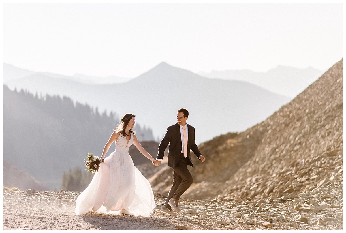 Clint grabbed his bride's hand as they began running down the trail of Ophir Pass where they had just celebrated their nuptials with a private first look in the San Juan Mountains with only their intimate wedding photographer Maddie Mae as the sun rose over Telluride.