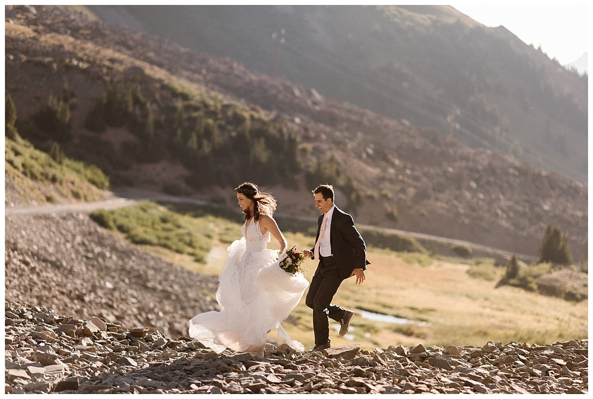 Continuing on down the rocky path in their hiking boots and wedding clothes, this adventurous couple threw tradition to the wind and celebrated their private first look as sunrise up Ophir Pass before their intimate wedding ceremony with only their traveling elopement photographer Maddie Mae.