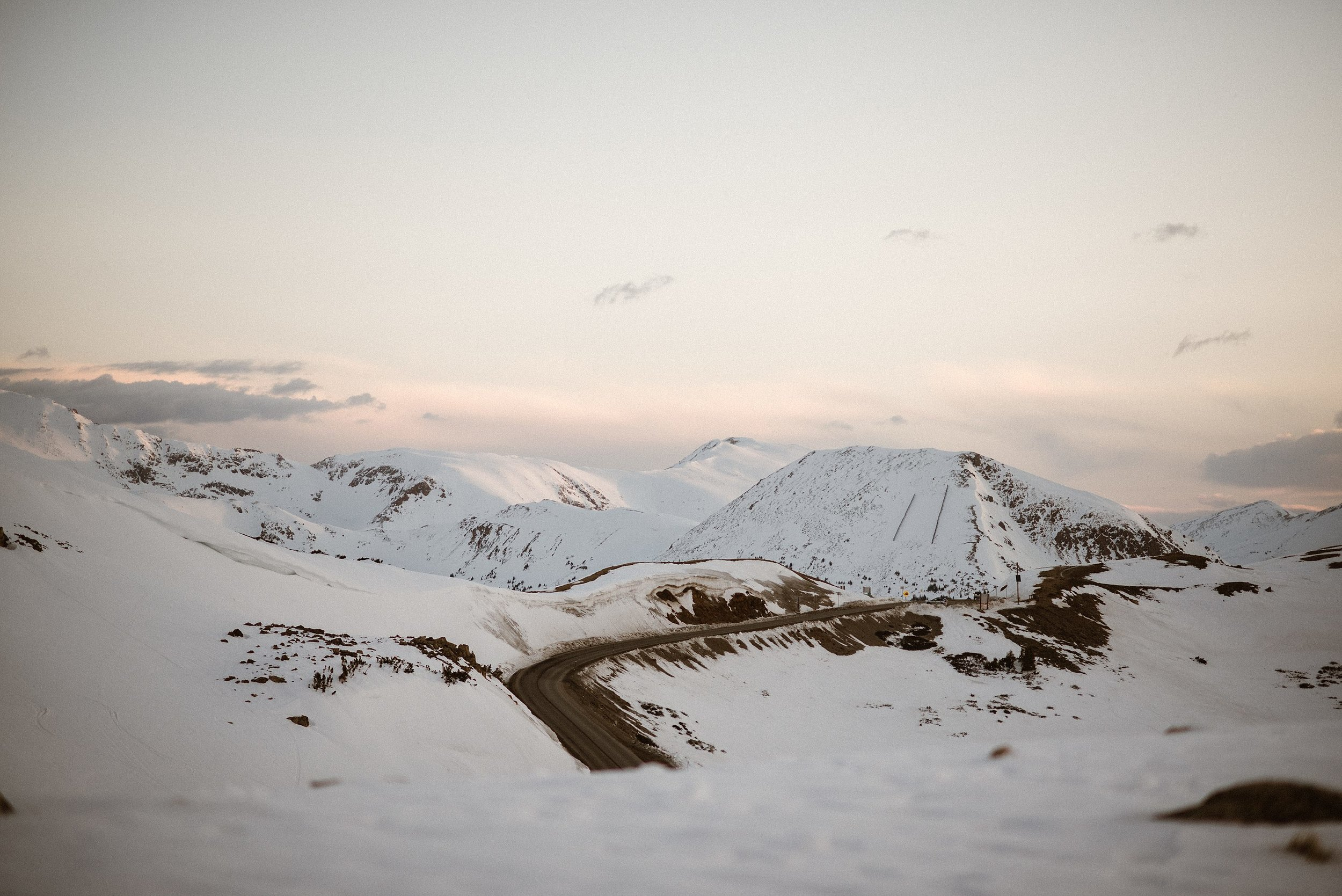Starting the morning up Loveland Pass with the sun just starting to rise over the mountains, the pink alpine glow setting the stage for this intimate snowy elopement. Photos by intimate wedding photographer Maddie Mae.