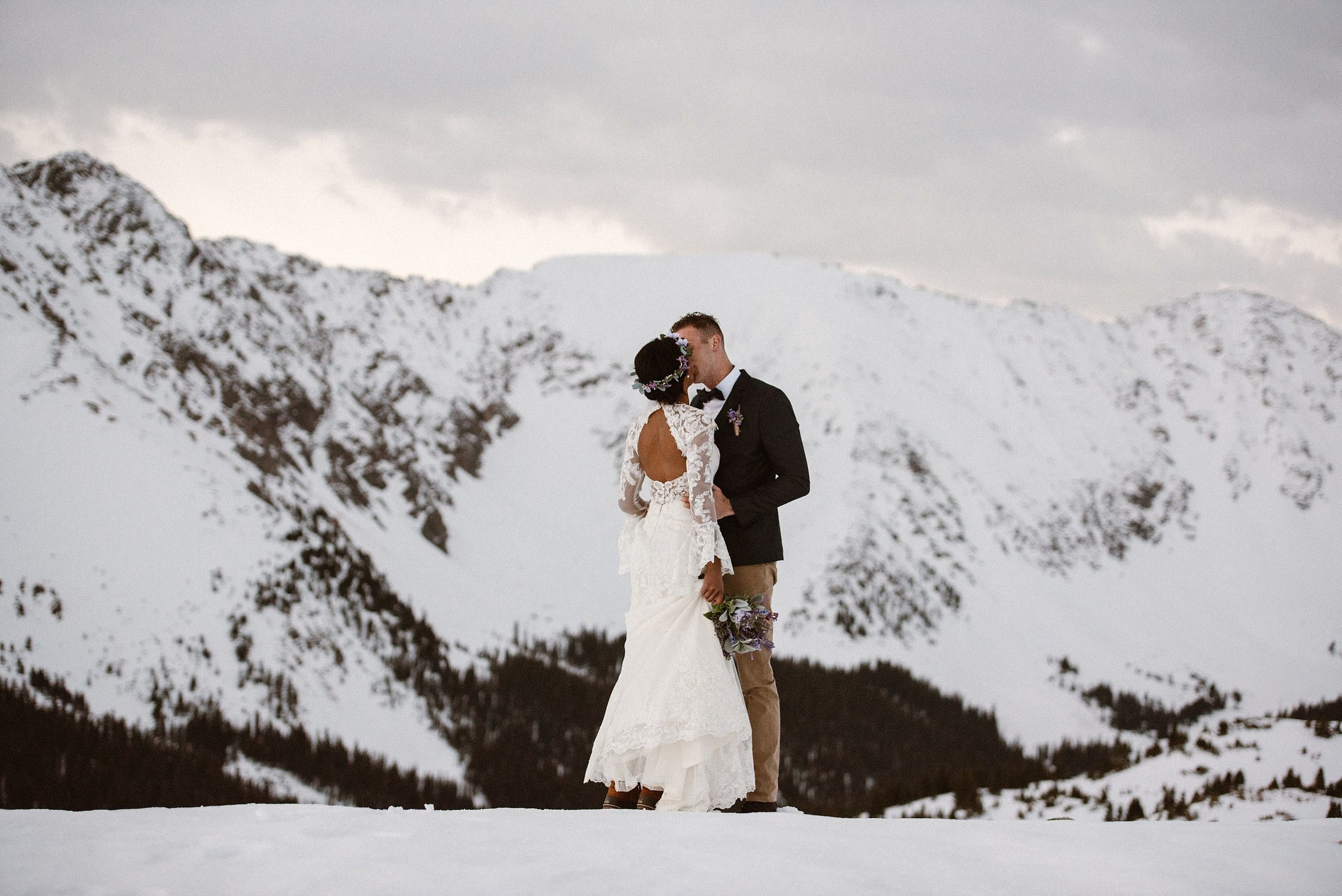Jared excitement couldn't be contained as he laid eyes on his stunning mountain bride. Donning a simple flower crown and a backless white lace dress, this was the woman he was about profess his love to. Photos of this intimate snowy elopement up Loveland Pass photographed by Maddie Mae.