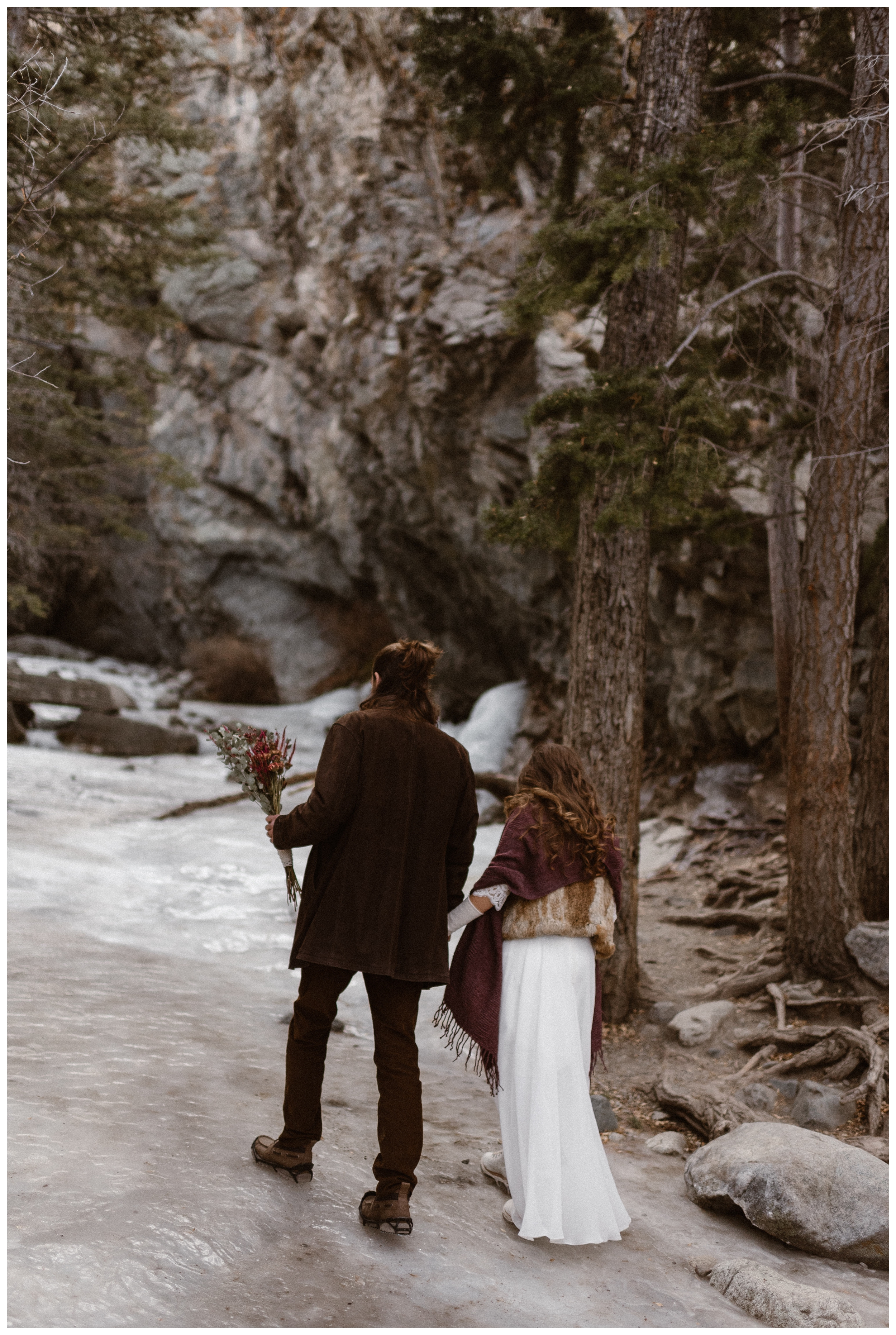 Olivia and Justin hike up to frozen Zapata Falls outside Great Sand Dunes National Park before their winter elopement. Photo by Maddie Mae Photo, Adventures Instead.