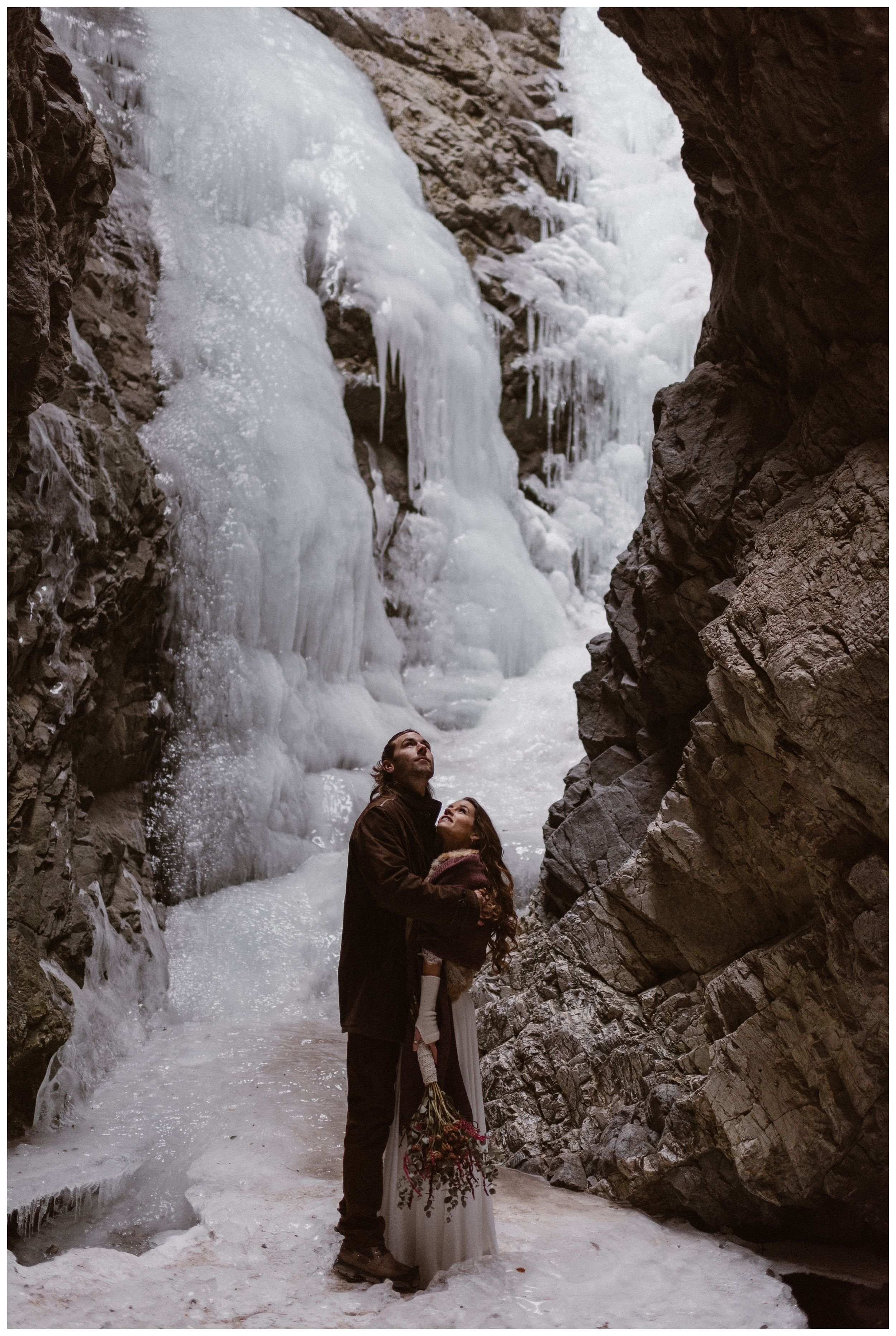 Ice cascades around Olivia and Justin from the frozen waterfall at Zapata Falls before their winter adventure elopement in Southern Colorado. Photo by Maddie Mae Photo, Adventures Instead.