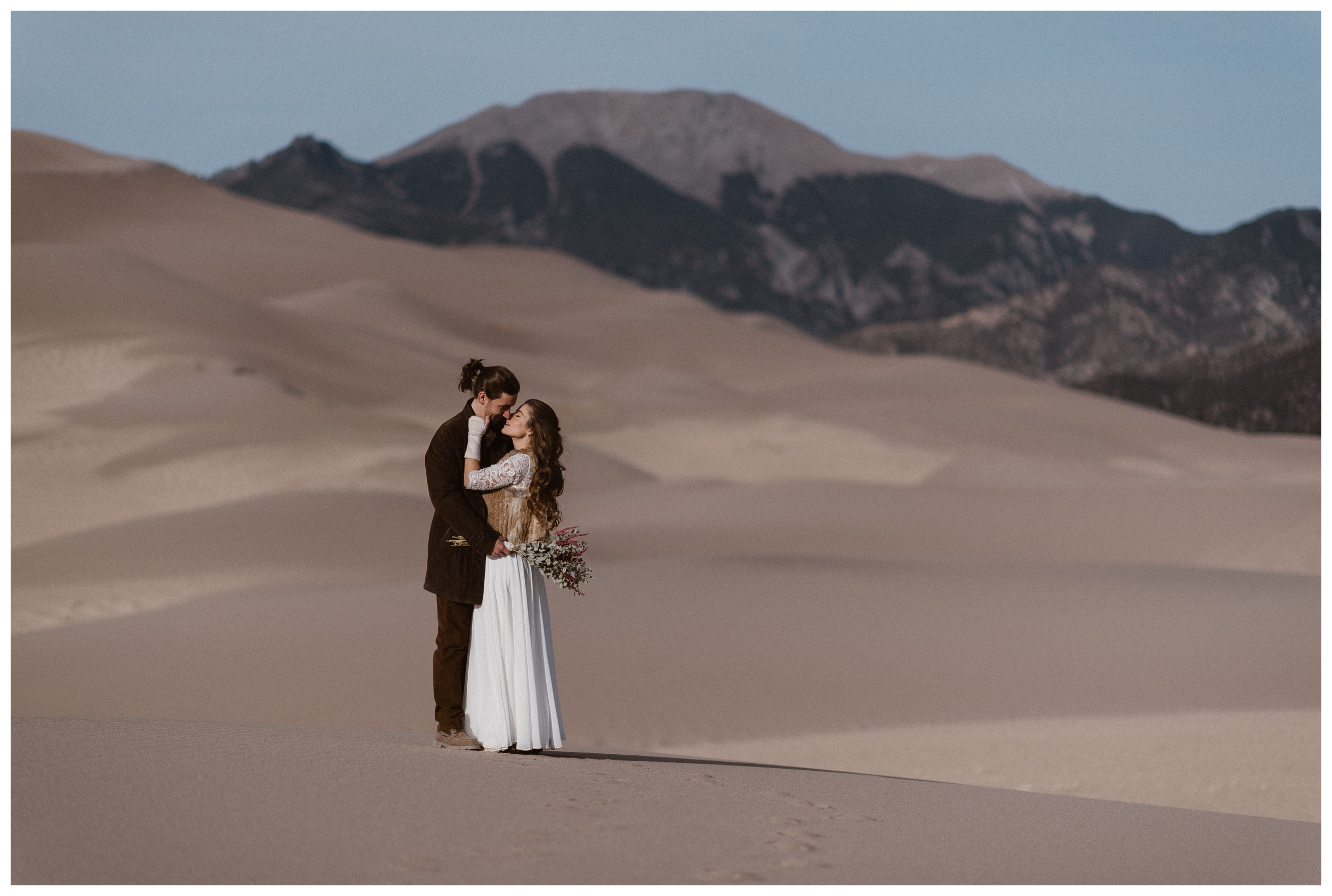 Olivia and Justin kiss at the Great Sand Dunes National Park before their winter elopement wedding ceremony. Photo by Maddie Mae Photo, Adventures Instead.