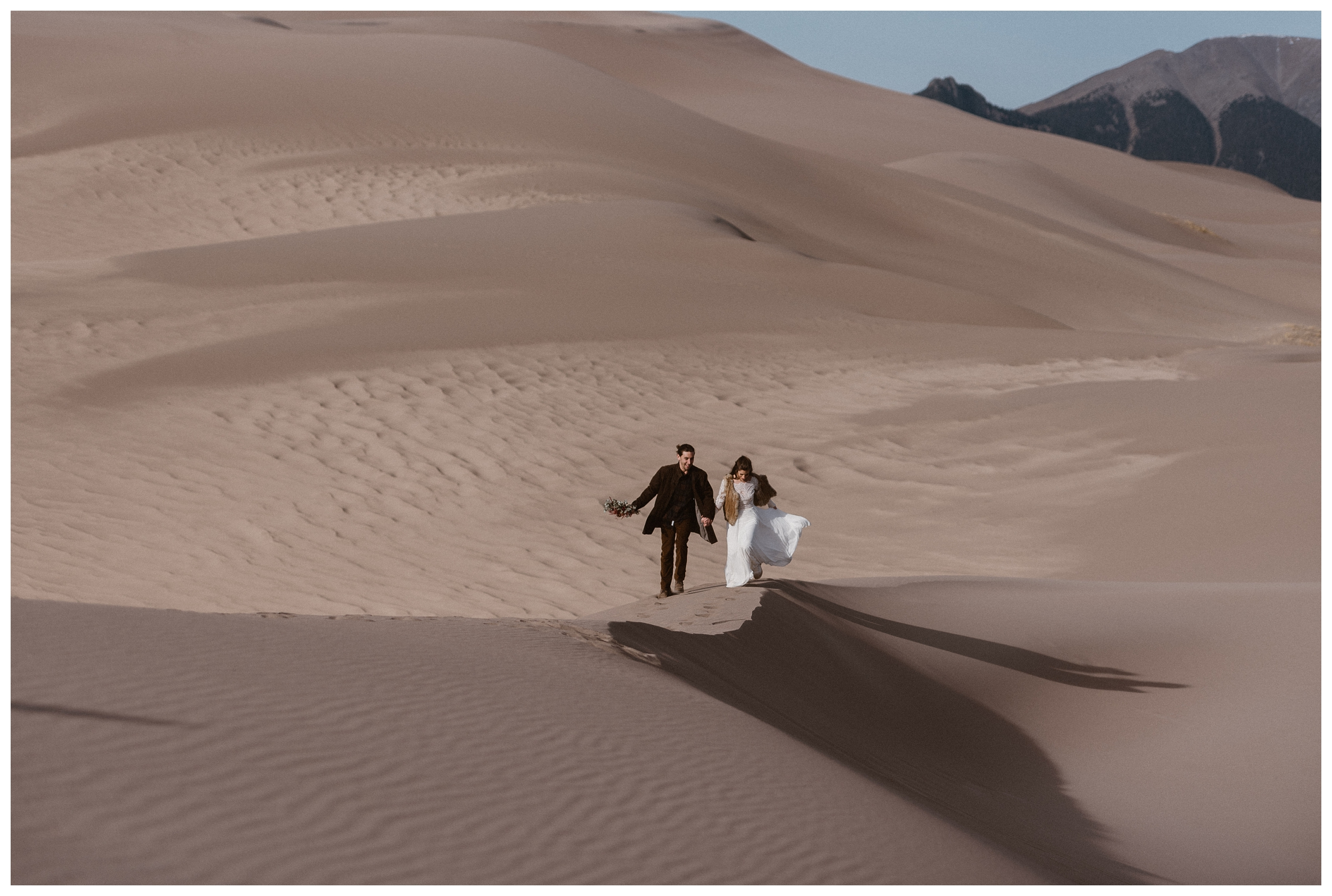 Olivia and Justin walk the Great Sand Dunes National Park together during their adventure elopement. Photo by Maddie Mae Photo, Adventures Instead.