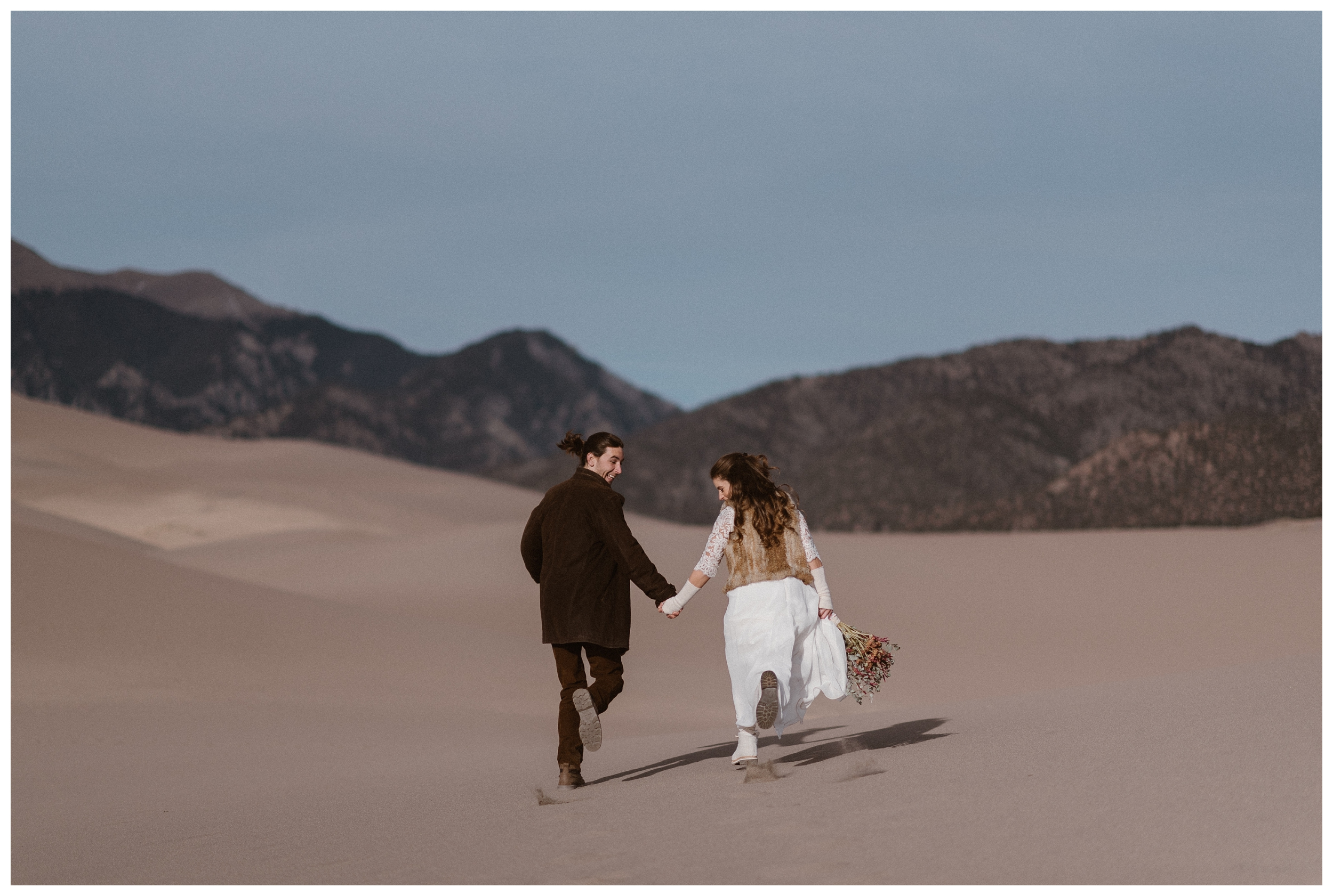 Olivia and Justin run hand in hand as bride and groom before their winter wedding ceremony at the Great Sand Dunes. Photo by Maddie Mae Photo, Adventures Instead.