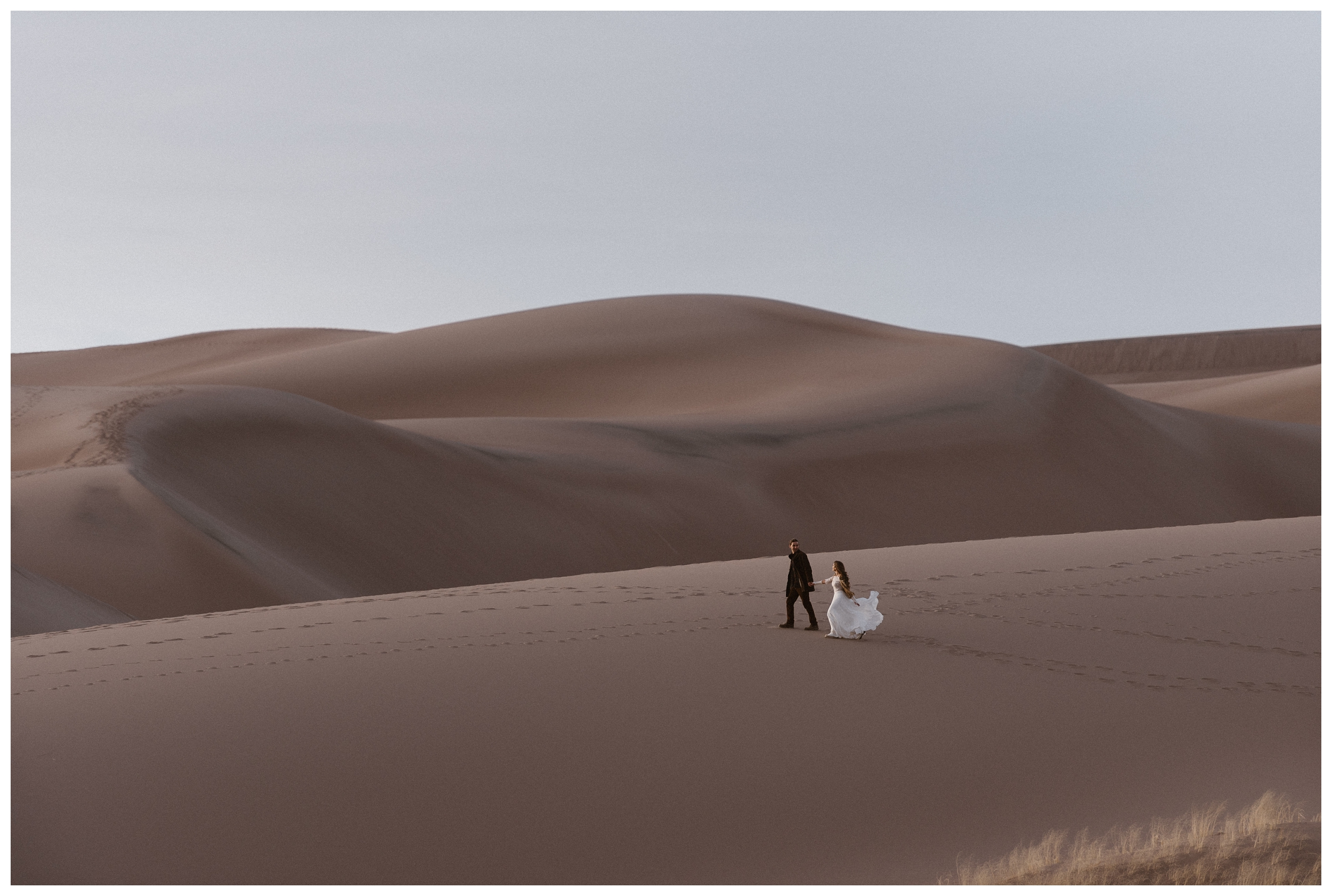 Bride and groom walk through the Great Sand Dunes National Park after their intimate elopement wedding ceremony. Photo by Maddie Mae Photo, Adventures Instead.