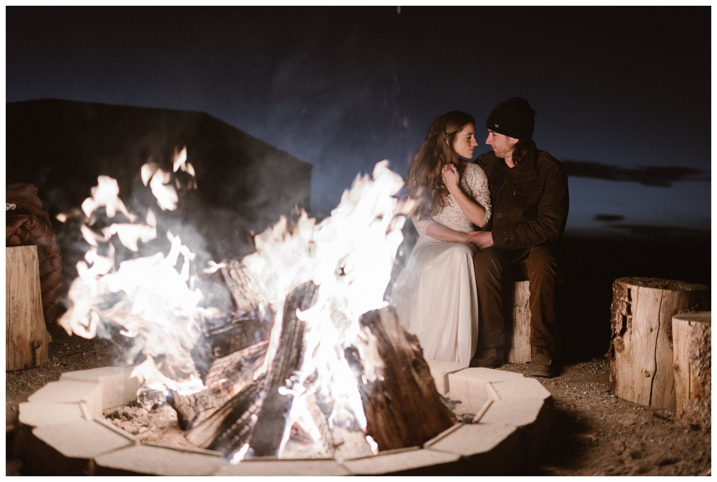 Newly wed couple Olivia and Justin sit by the fire outside Great Sand Dunes National Park after their winter elopement. Photo by Maddie Mae Photo, Adventures Instead.