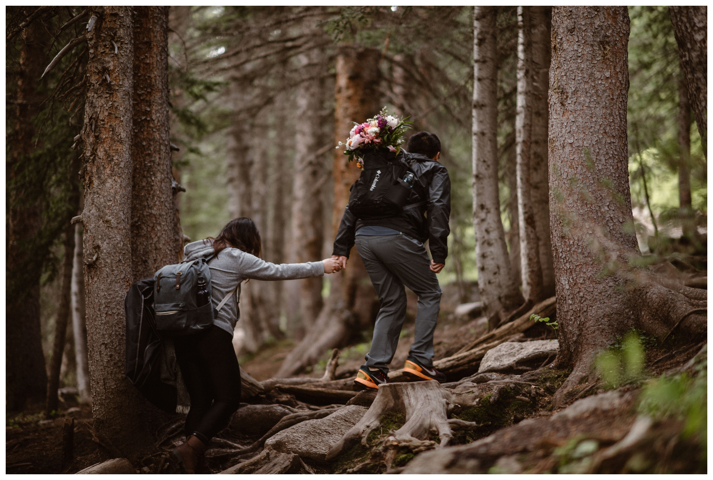 Leslie and Jinson help each other over the rocky terrain on the trail to Gem Lake outside Estes Park Colorado. Photo by Maddie Mae Photo, Adventure Instead.