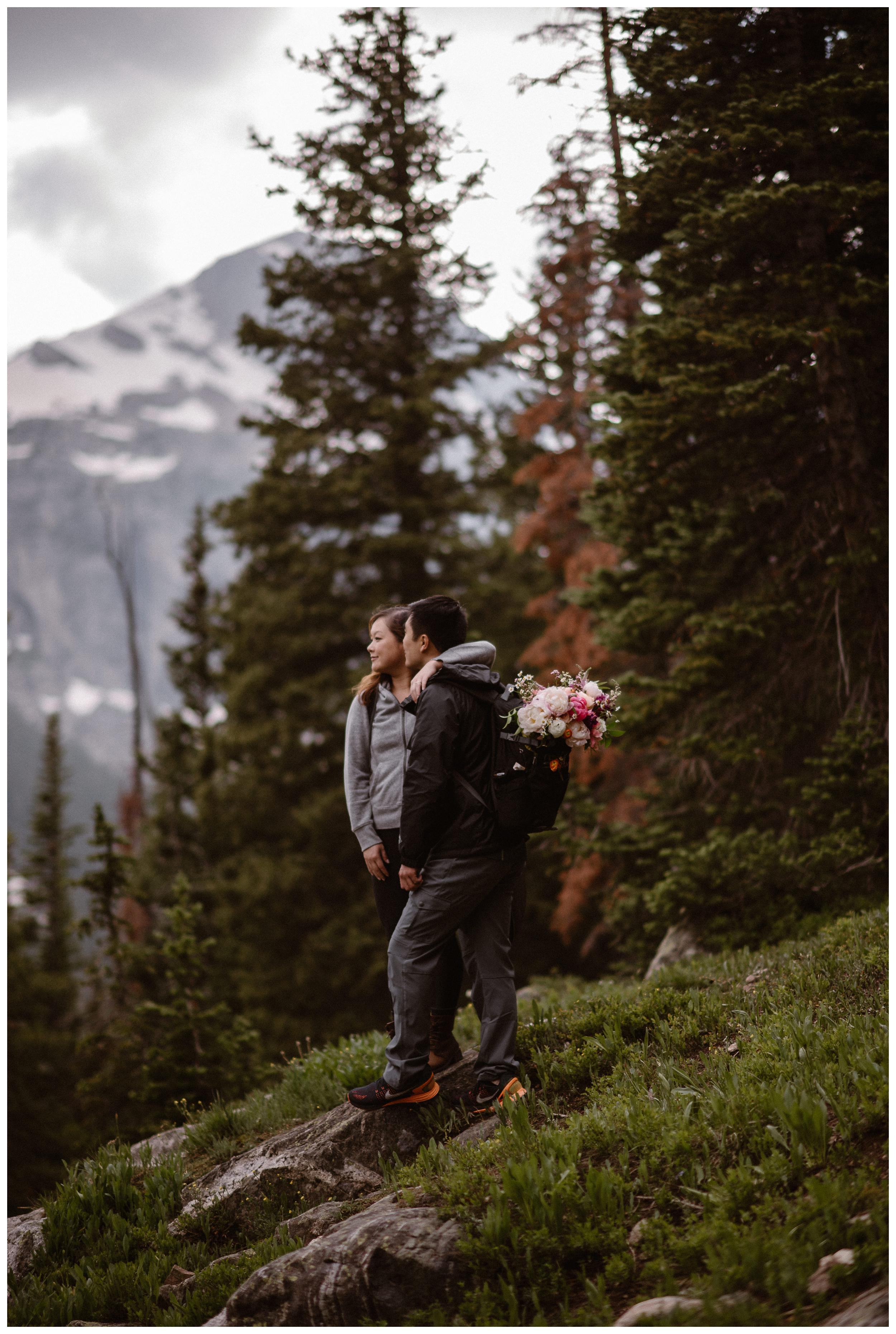 Leslie and Jinson stop as they hike up the Gem Lake Trail for their hiking adventure elopement ceremony to survey the Rocky Mountains. Photo by Maddie Mae Photo, Adventure Instead.