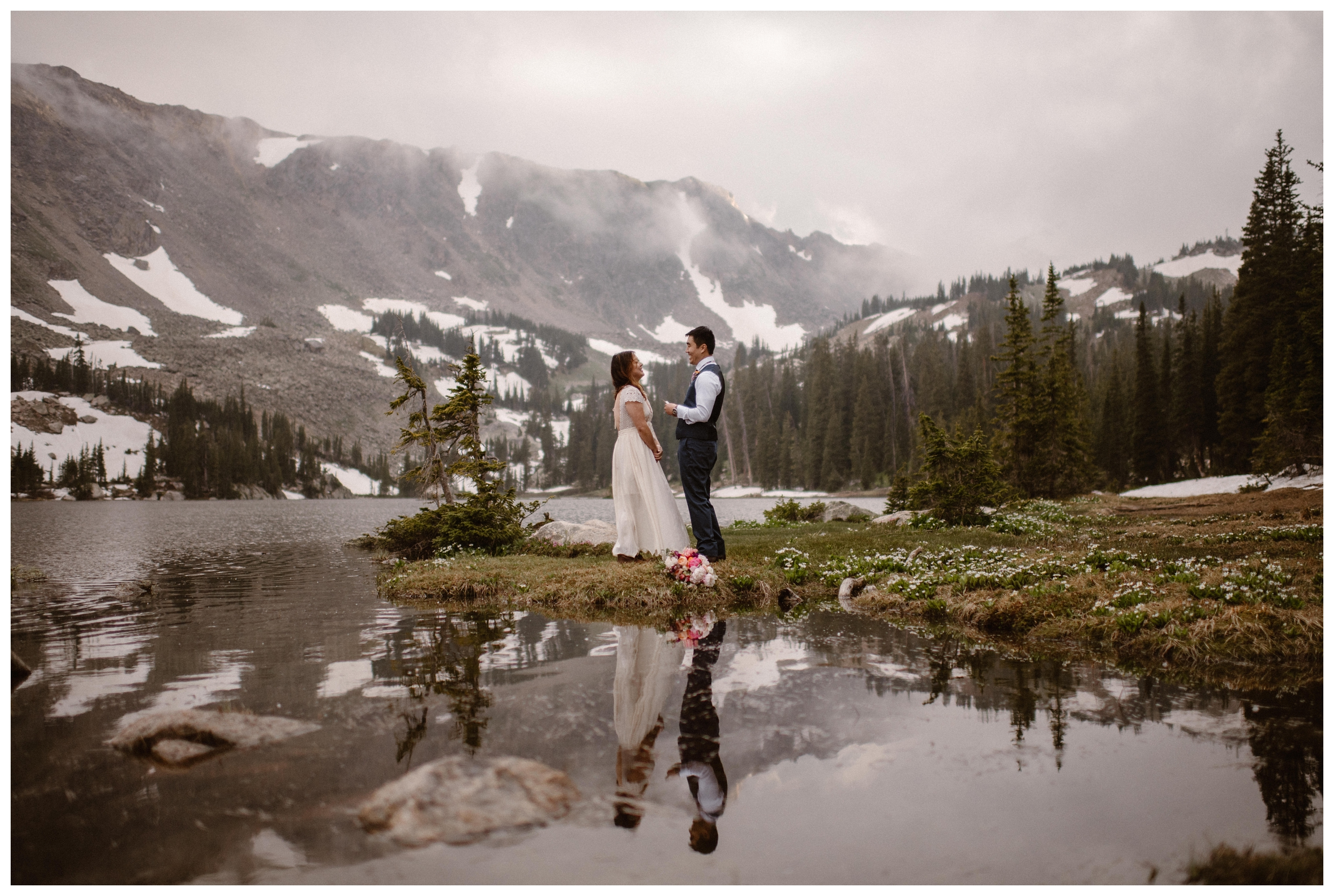 Clouds and snow dot the mountain cliffs behind Leslie and Jinson as they say their vows at Gem Lake during their elopement ceremony. Photo by Maddie Mae Photo, Adventure Instead.