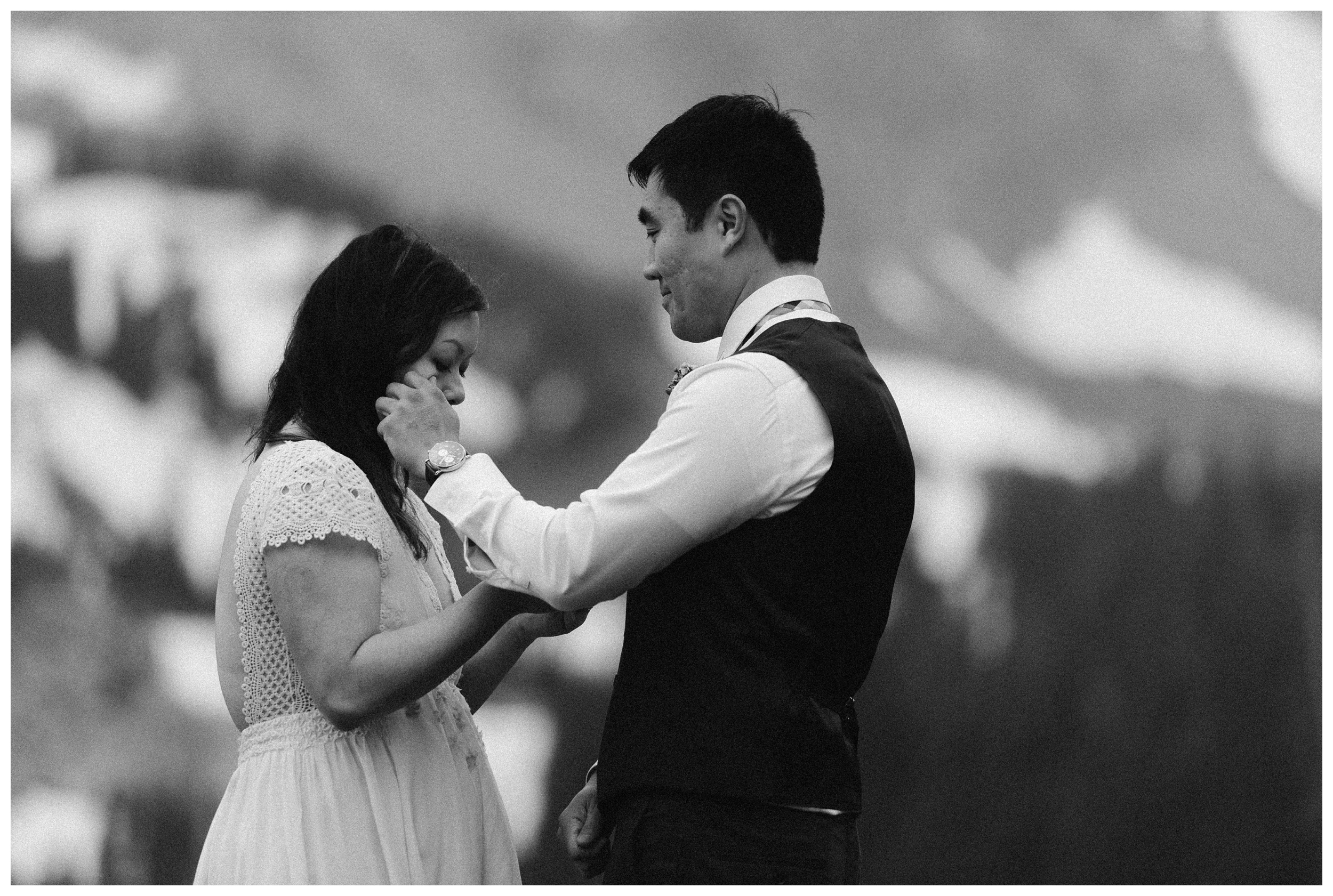 Jinson wipes a tear off the face of his bride as they exchange vows on the shores of high alpine lake Gem Lake outside Estes Park Colorado. Photo by Maddie Mae Photo, Adventure Instead.