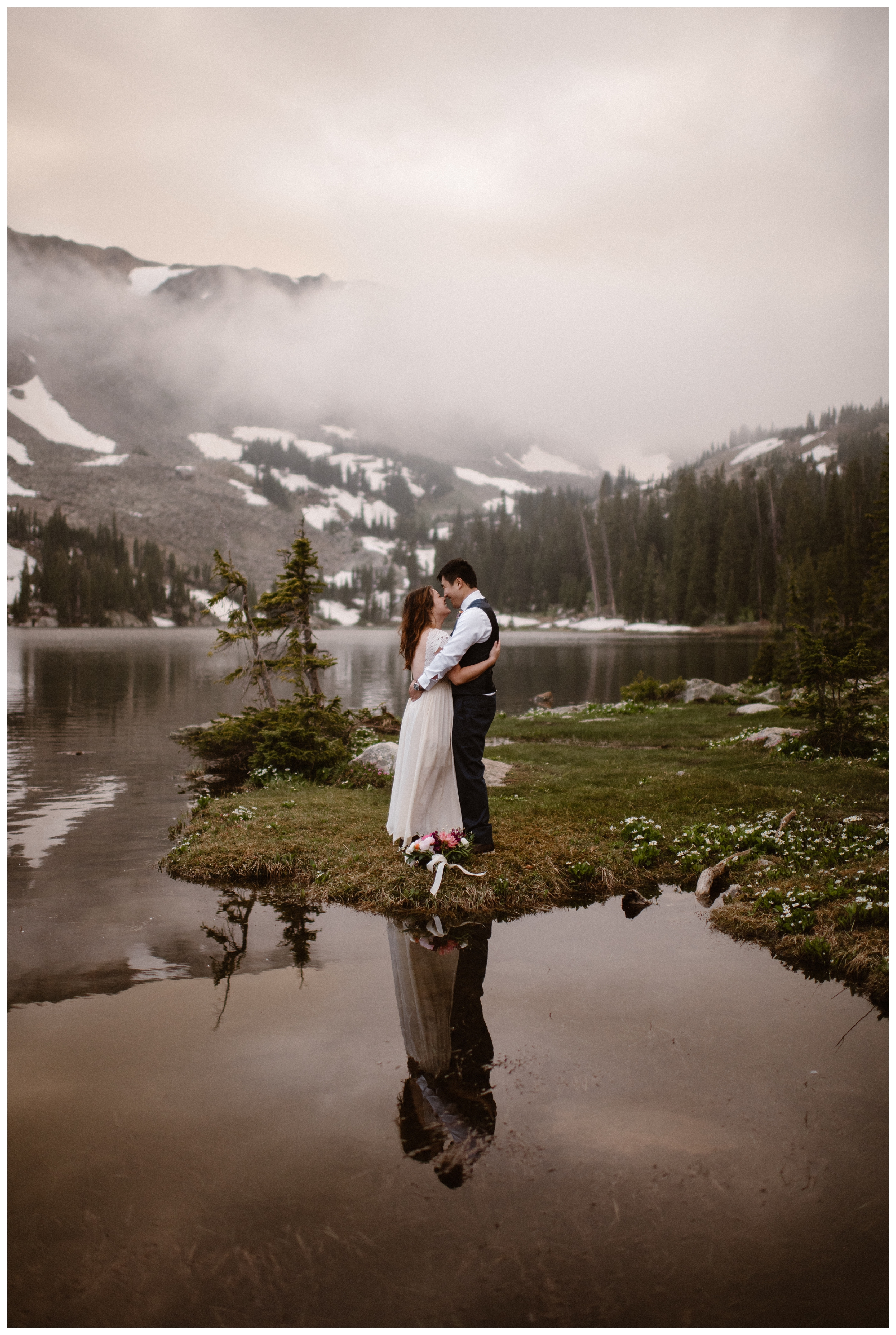 Snow dots the cliffs and clouds dance around Leslie and Jinson after their high alpine lake elopement ceremony at Gem Lake. Photo by Maddie Mae Photo, Adventure Instead.