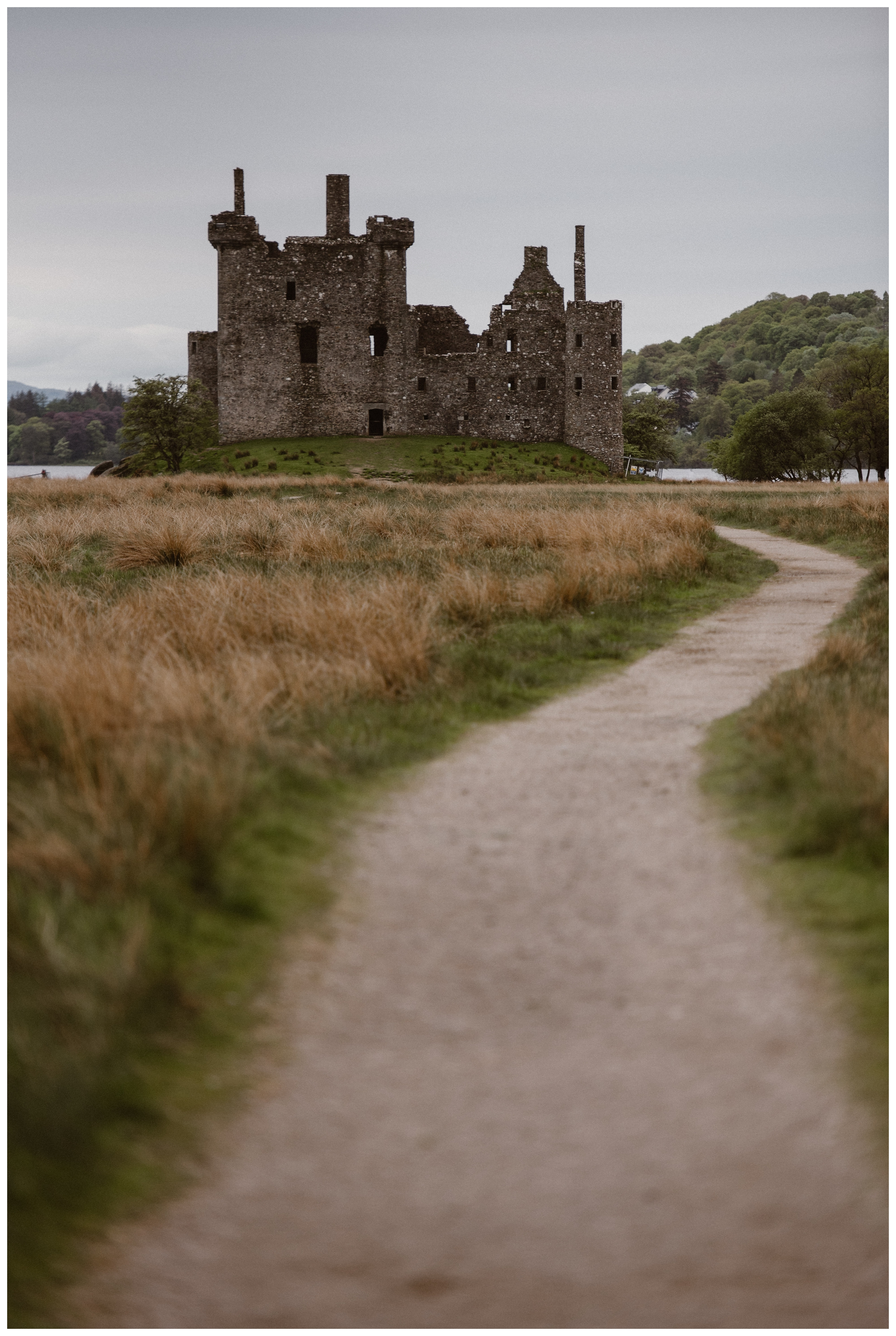 The ruins of Kilchurn Castle stand in the Scottish Highlands where Elissa and Daniel planned a destination adventure elopement. Photo by Maddie Mae, Adventure Instead.