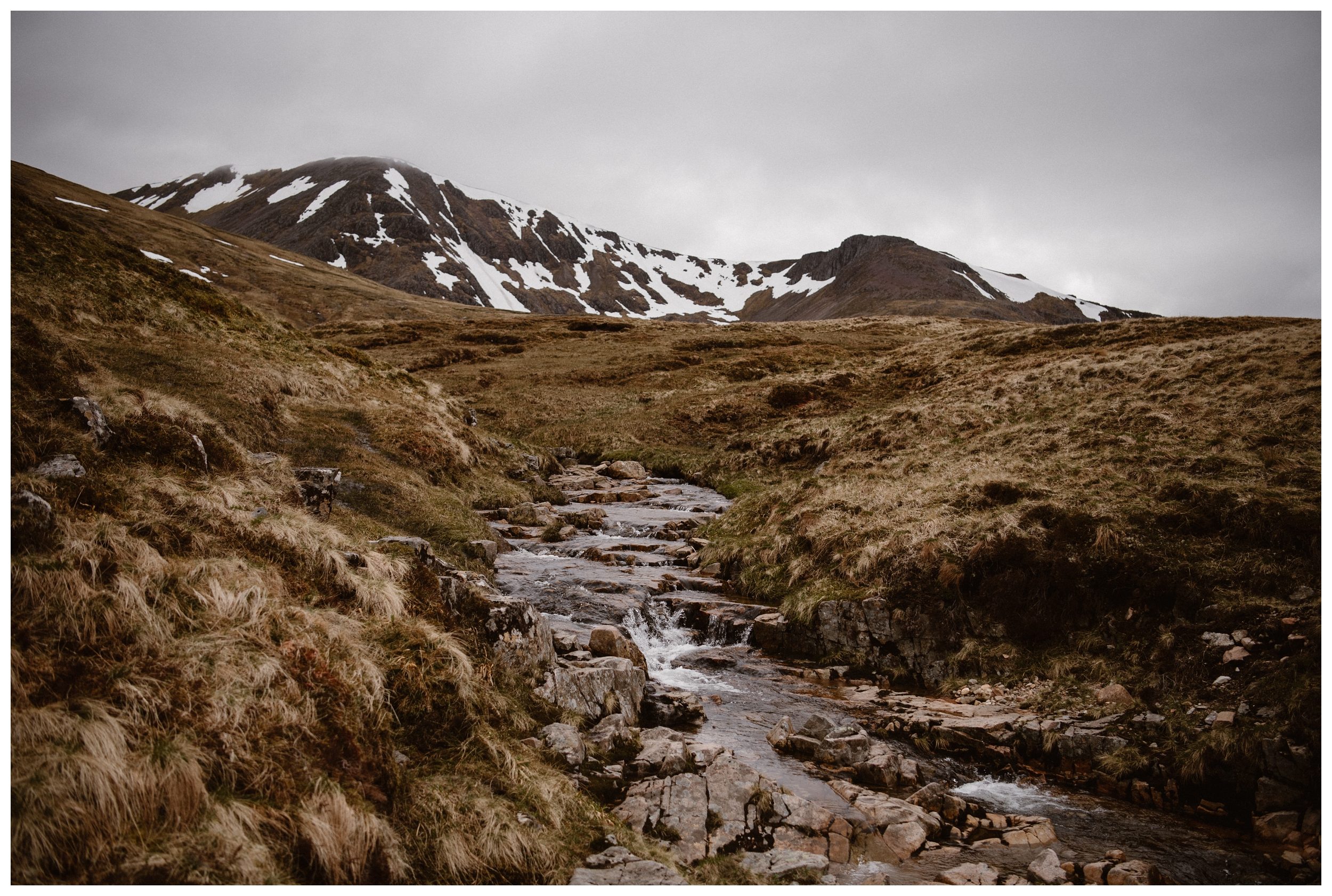 A river runs through the hills of the Scottish Highlands outside Kilchurn Castle, near Loch Awe, Argyll and Bute in Scotland. Photo by Maddie Mae, Adventure Instead.